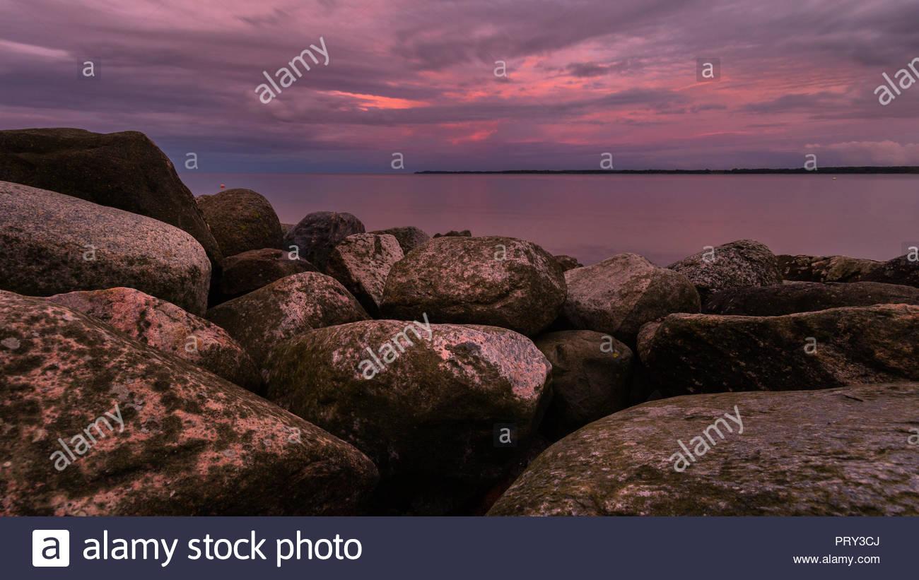 Weite Sicht auf die Ostsee über eine Felsbrandung im Sonnenuntergang Stockbild