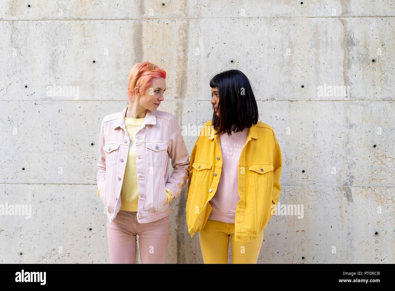 Zwei alternative Freunde Spaß haben, tragen gelbe und rosa jeans Kleidung, von Angesicht zu Angesicht Stockbild