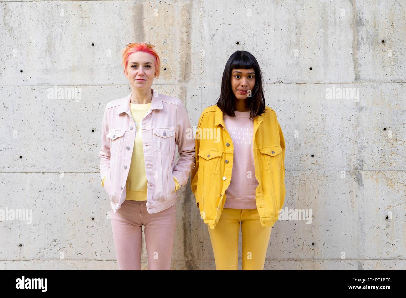 Zwei alternative Freunde Spaß haben, tragen gelbe und rosa jeans Kleidung Stockbild