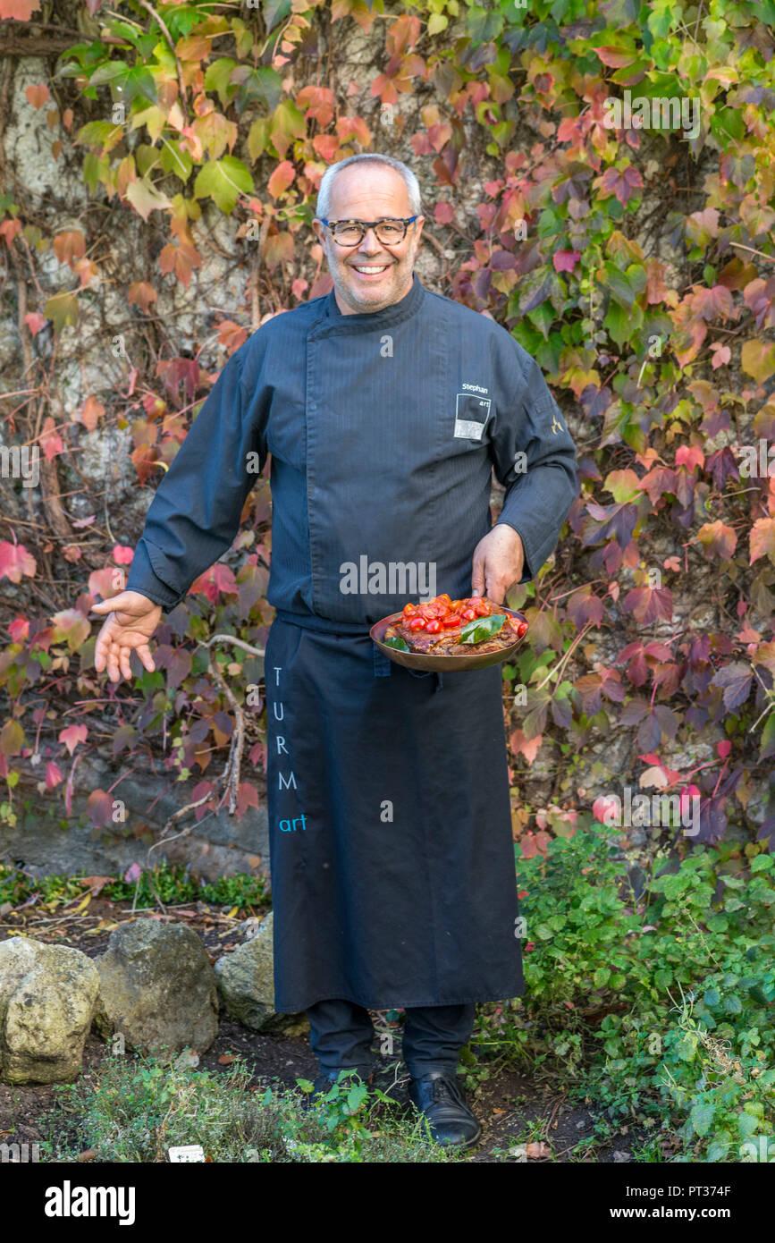 Küchenchef Stefan Pramstaller mit geschmorten Schweinebauch, Romantik Hotel Turm, Völs am Schlern, Seiser Alm, Eisacktal, Südtirol, Italien Stockbild