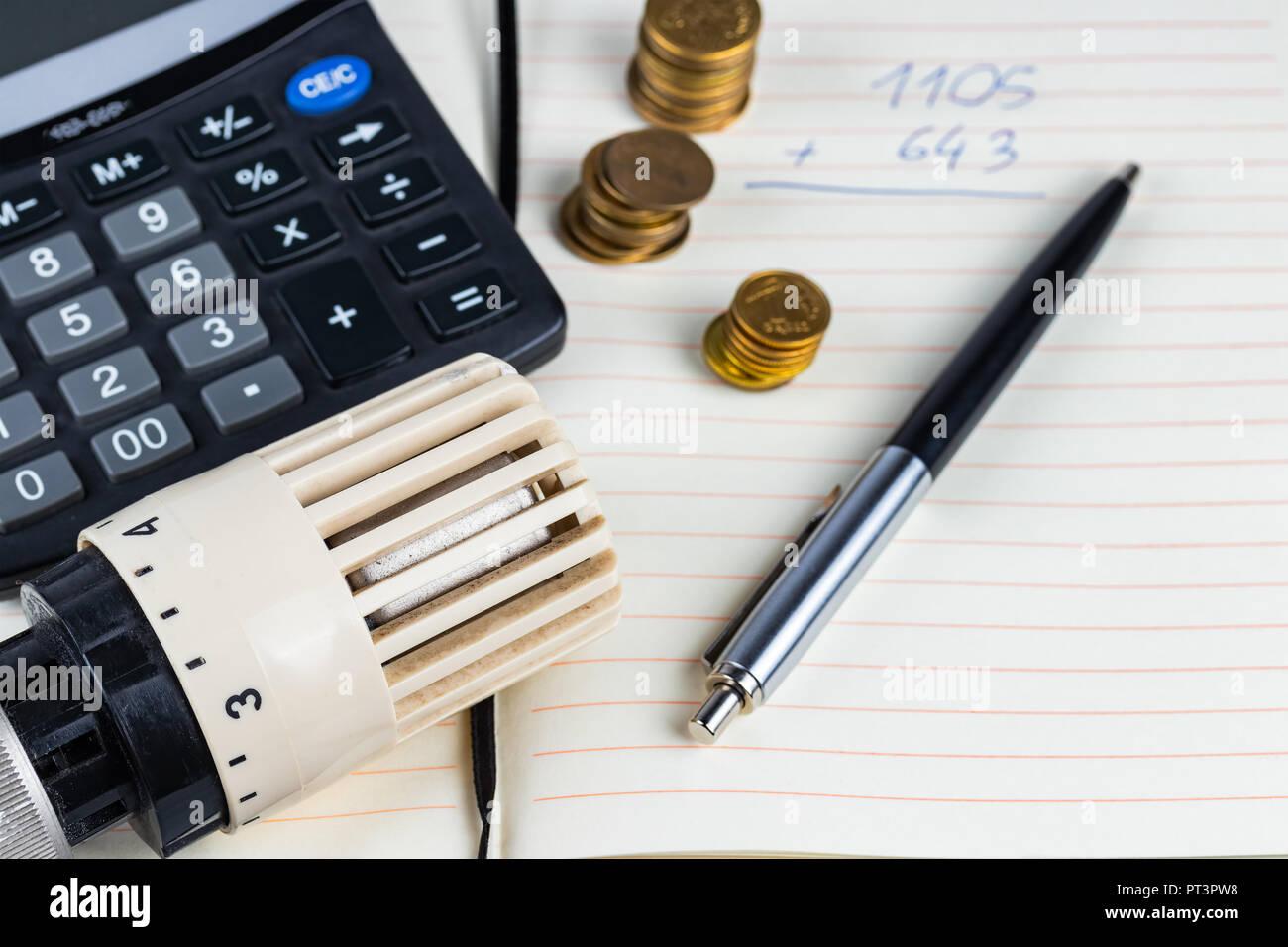 Home Wärme oder Ausgaben Konzept. Kühler Regler mit Münzen und Rechner auf einem Notizblock. Stockbild
