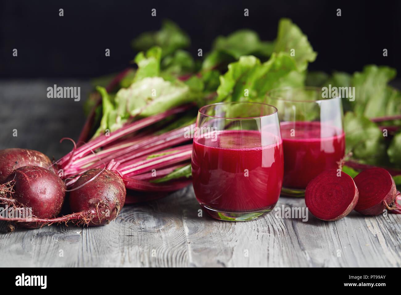 Detox Saft mit frisch gepflückten Bündel von Rote Bete. Frische rote Rüben auf einem Holztisch. Stockbild