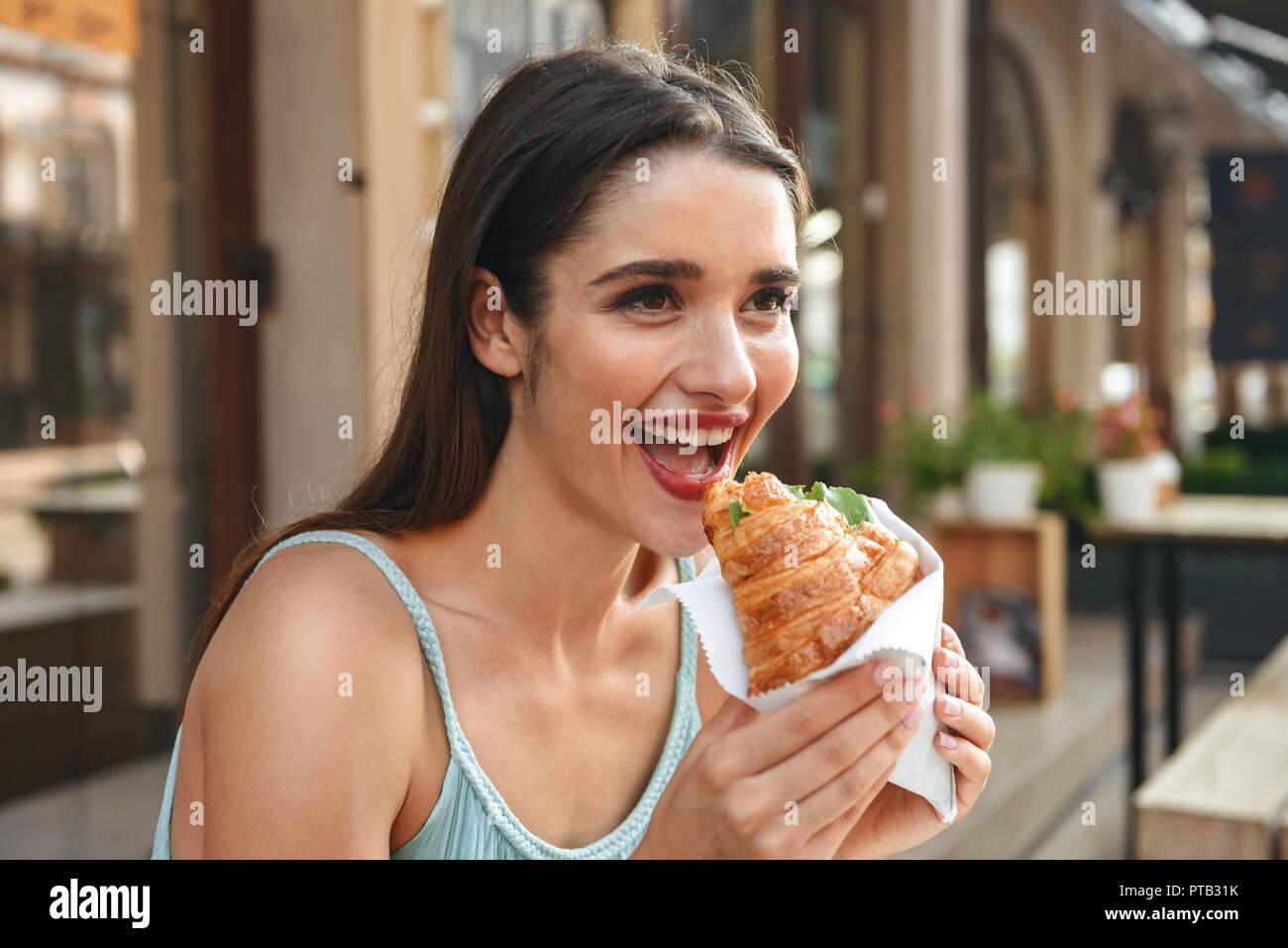 Bild der junge lächelnde Frau sitzt im Cafe im Freien während des Essens Croissant. Stockfoto
