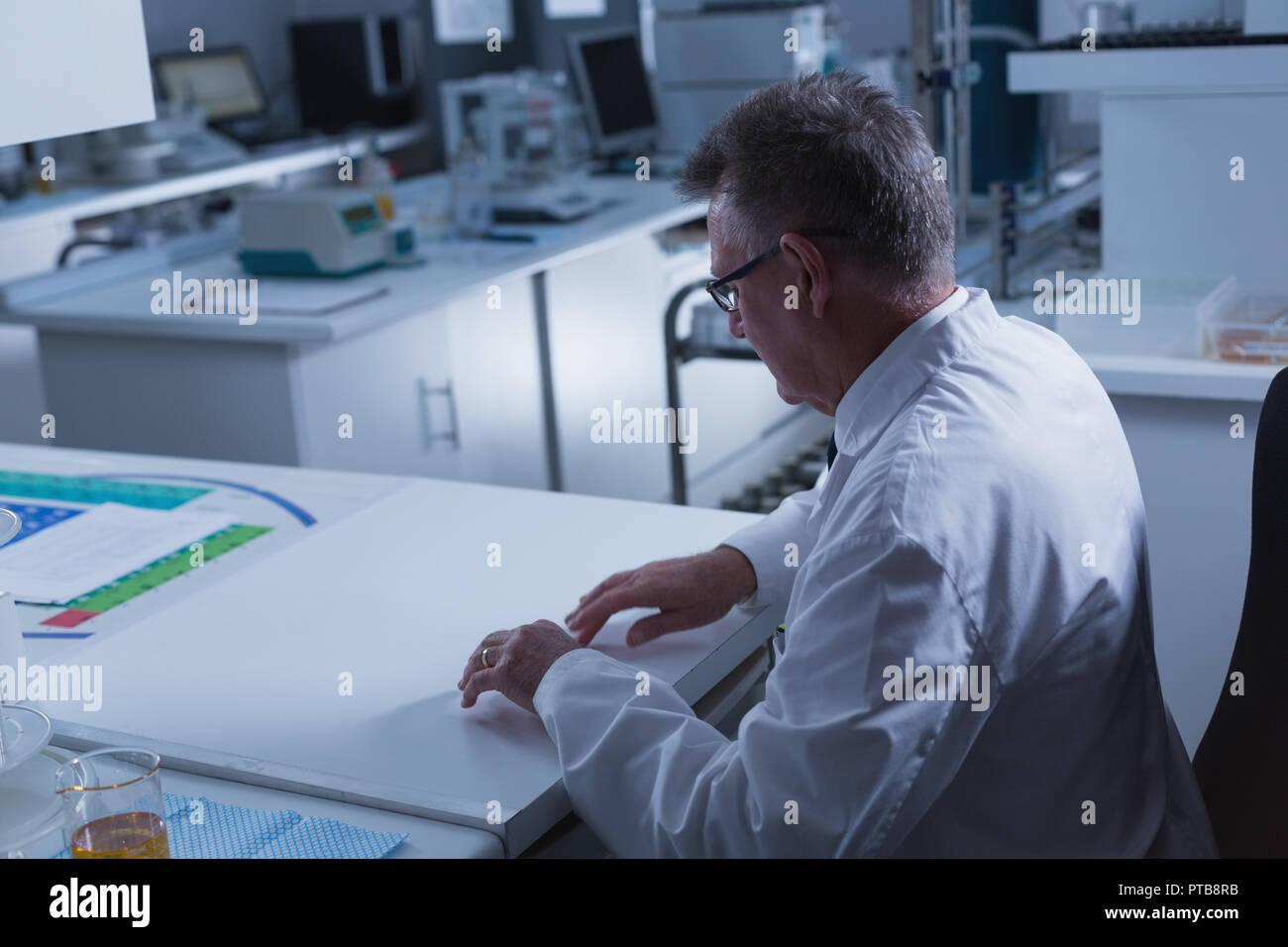 Männliche Wissenschaftler mit UNSEEN neue Technologie am Schreibtisch Stockbild