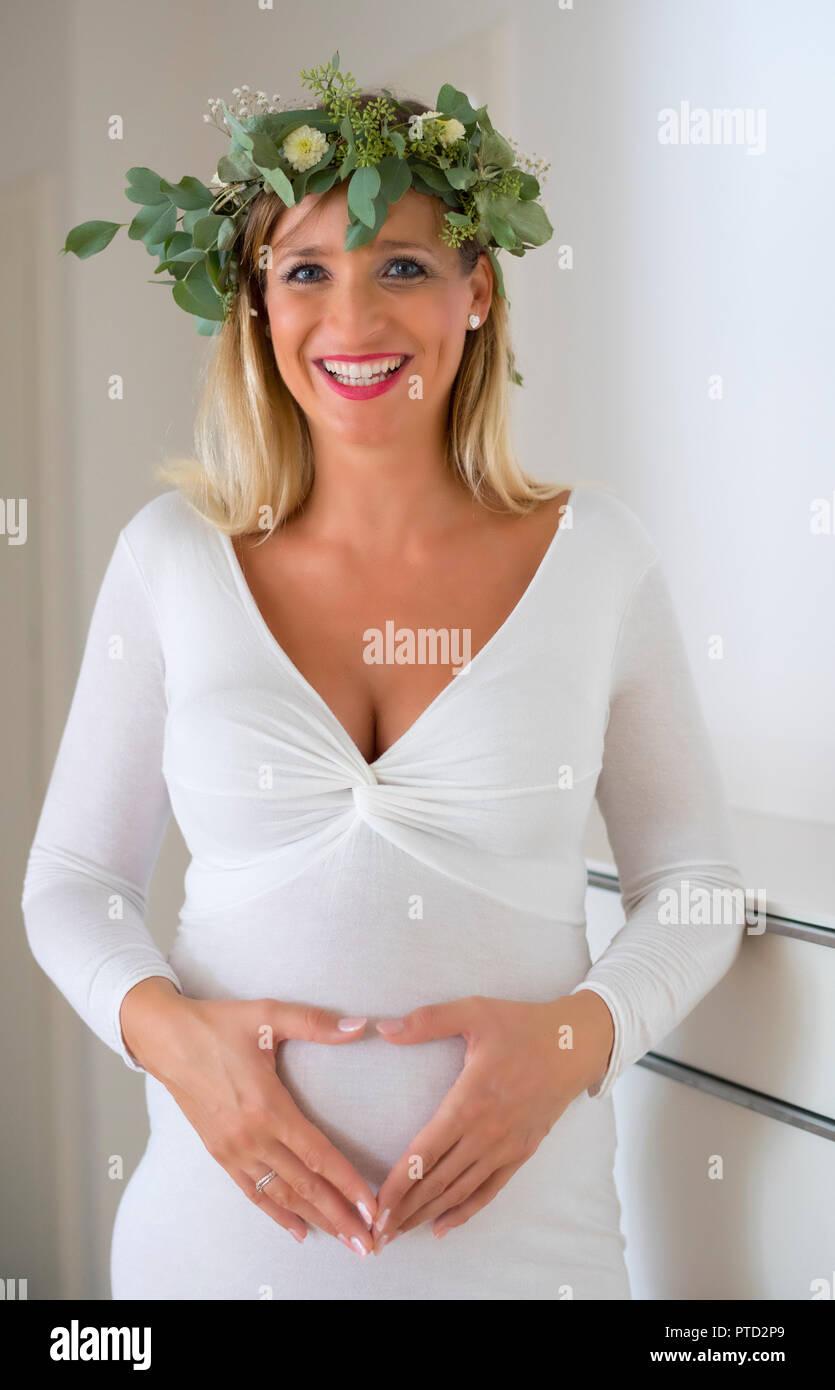 Frau, Braut, mit Kranz aus Blumen, neun Monate schwanger, mit den Händen bilden ein Herz vor Ihren schwangeren Bauch, Deutschland Stockfoto