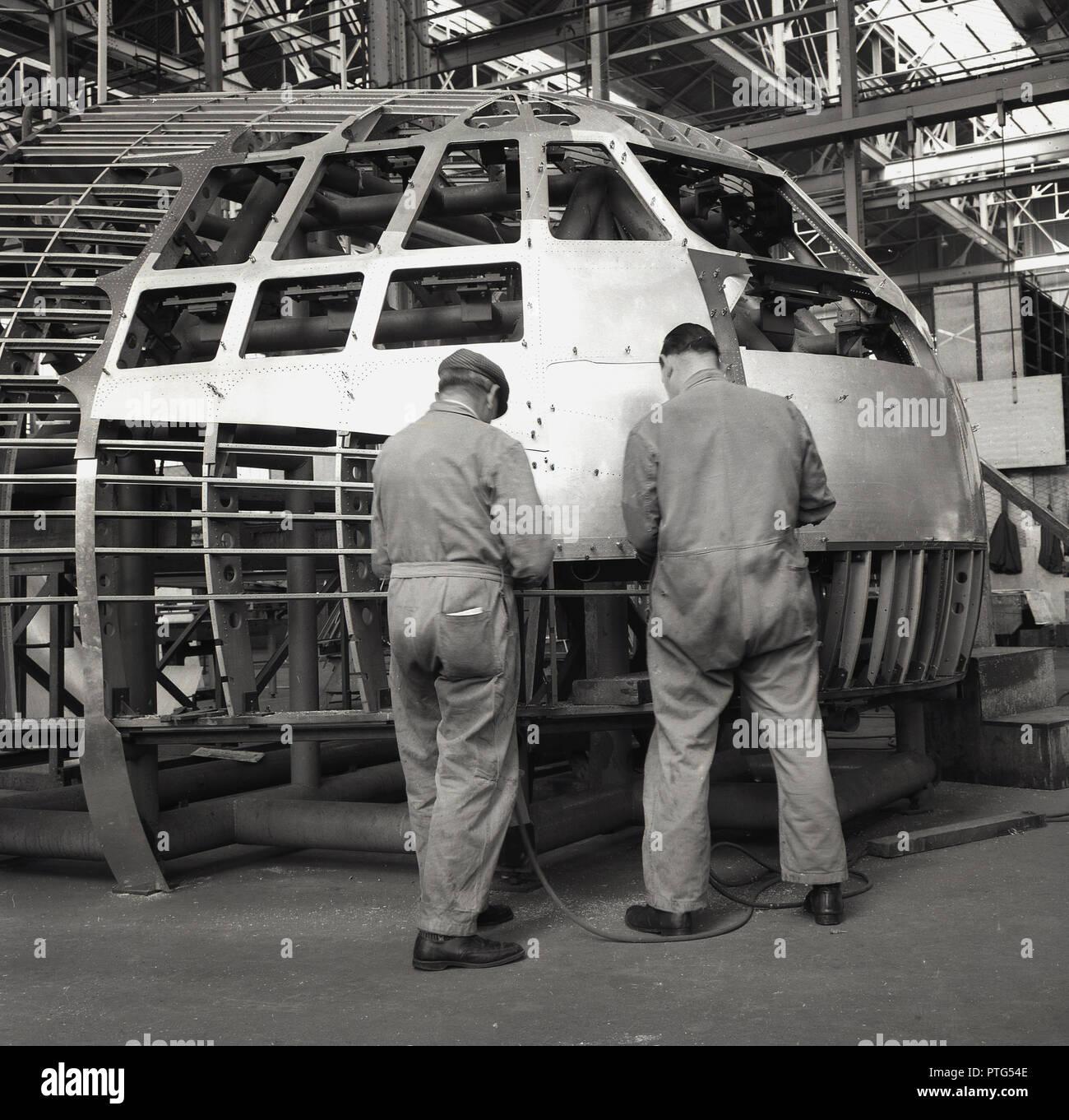 1950, historische, Luftfahrt, zwei männliche Mechanik oder Ingenieure in Overalls arbeiten an der äußeren Flugzeugcockpit innerhalb einer Fabrik für Luft- und Raumfahrt oder Aufhänger, England, UK. Stockbild