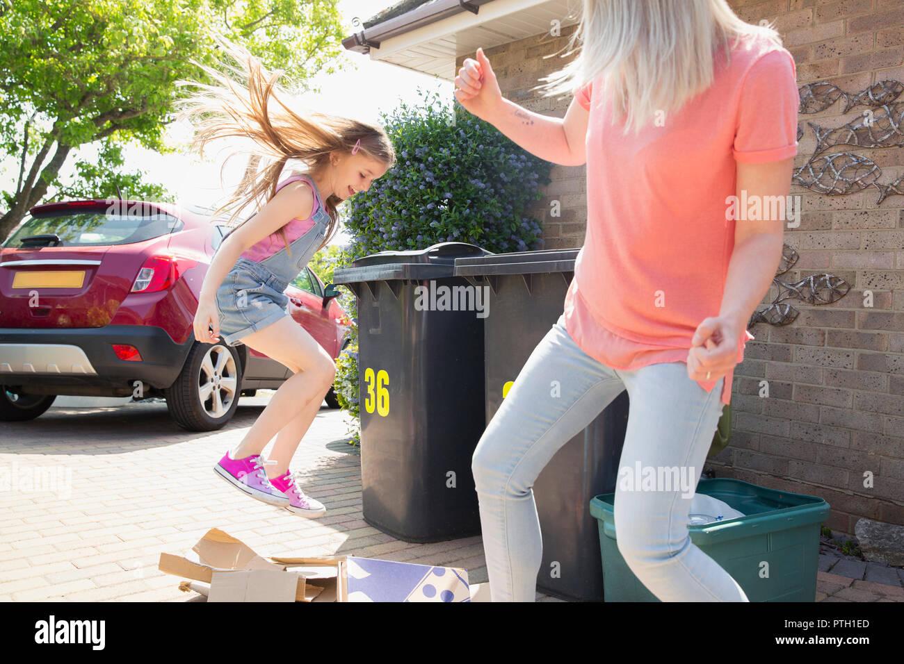 Mutter und Tochter, die Pappe für Recycling ausserhalb des Hauses Stockbild