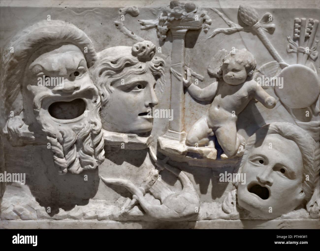 Doppelseitige Maske relief Roman 2. Jahrhundert AD (Bärtigen Comic- und unregelmäßige Dionysischen Maske stehen auf einem schmalen Sims, eine kleine Eros ist Ausgeflogen und prallt zurück in Horror aus der grotesken Masken. Der dionysische Attribute in der rechten oberen Ecke mit, Tympanon, Flöte und thyrsus Personal) Stockbild