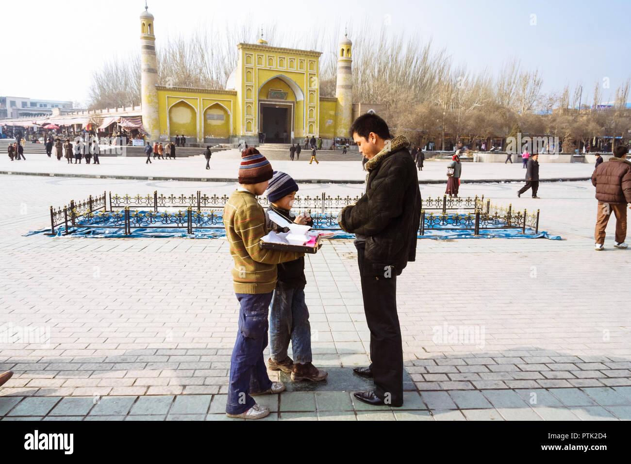 Kashgar, Xinjiang, China: Zwei uigurischen Kinder Süßigkeiten verkaufen gegenüber der gelben Fliesen- Id kah-Moschee (1442), die geistige und physische Herz der Cit Stockfoto