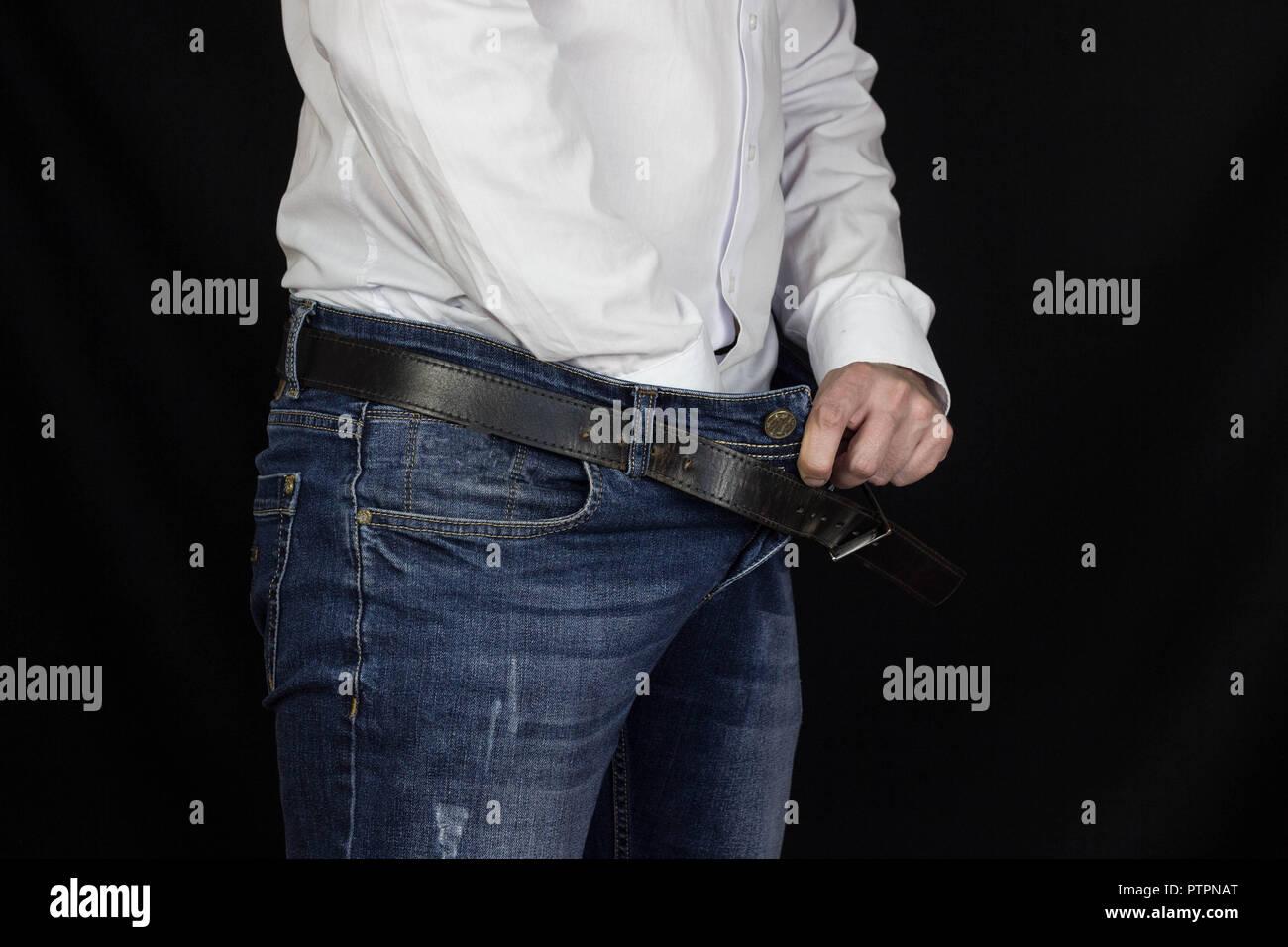 5bde5fd58000 Ein Mann in einem weißen Hemd und Jeans streckte seine Hand in seine Hose  und hält auf der Leiste, und in der Nähe schwarzer Hintergrund