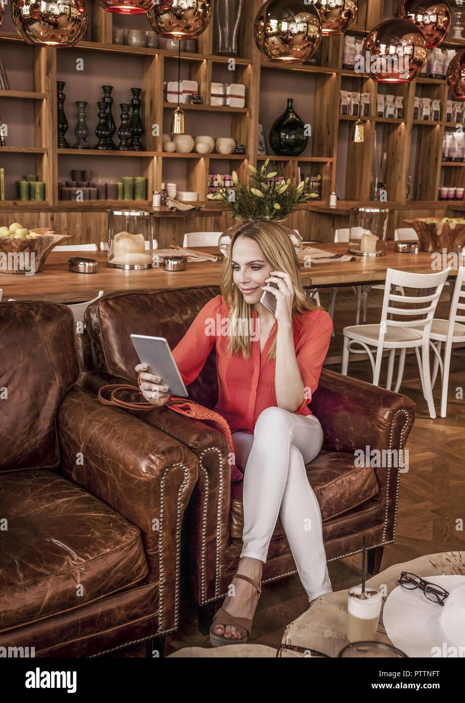 Frau im Kaffeehaus Mit Smartphone Und Tablet-PC (Model-Release) Stockfoto