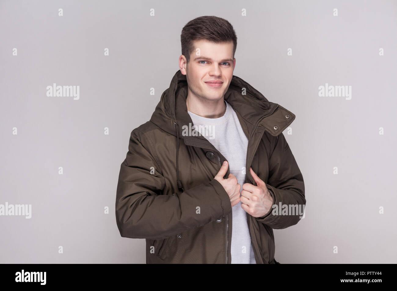 e285a0ba57a8 Porträt der jungen gutaussehenden Mann in Hellgrau Shirt und dunkelgrüne  Parka an Kamera mit Lächeln und