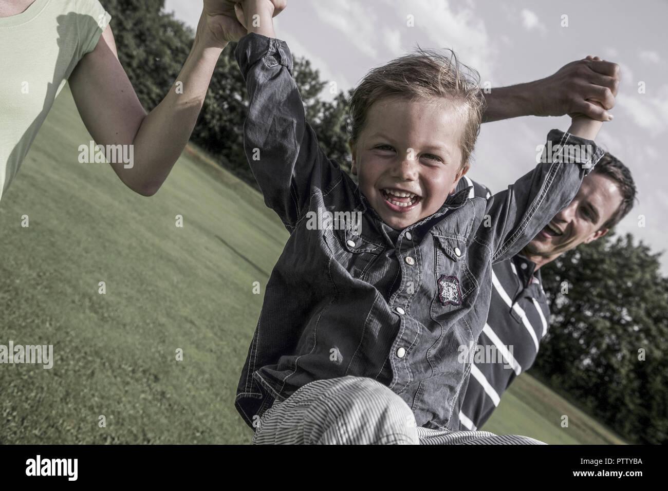 Eltern Zweisimmen Springenden Sohn eine Höhle Haenden (Model-Release) Stockbild