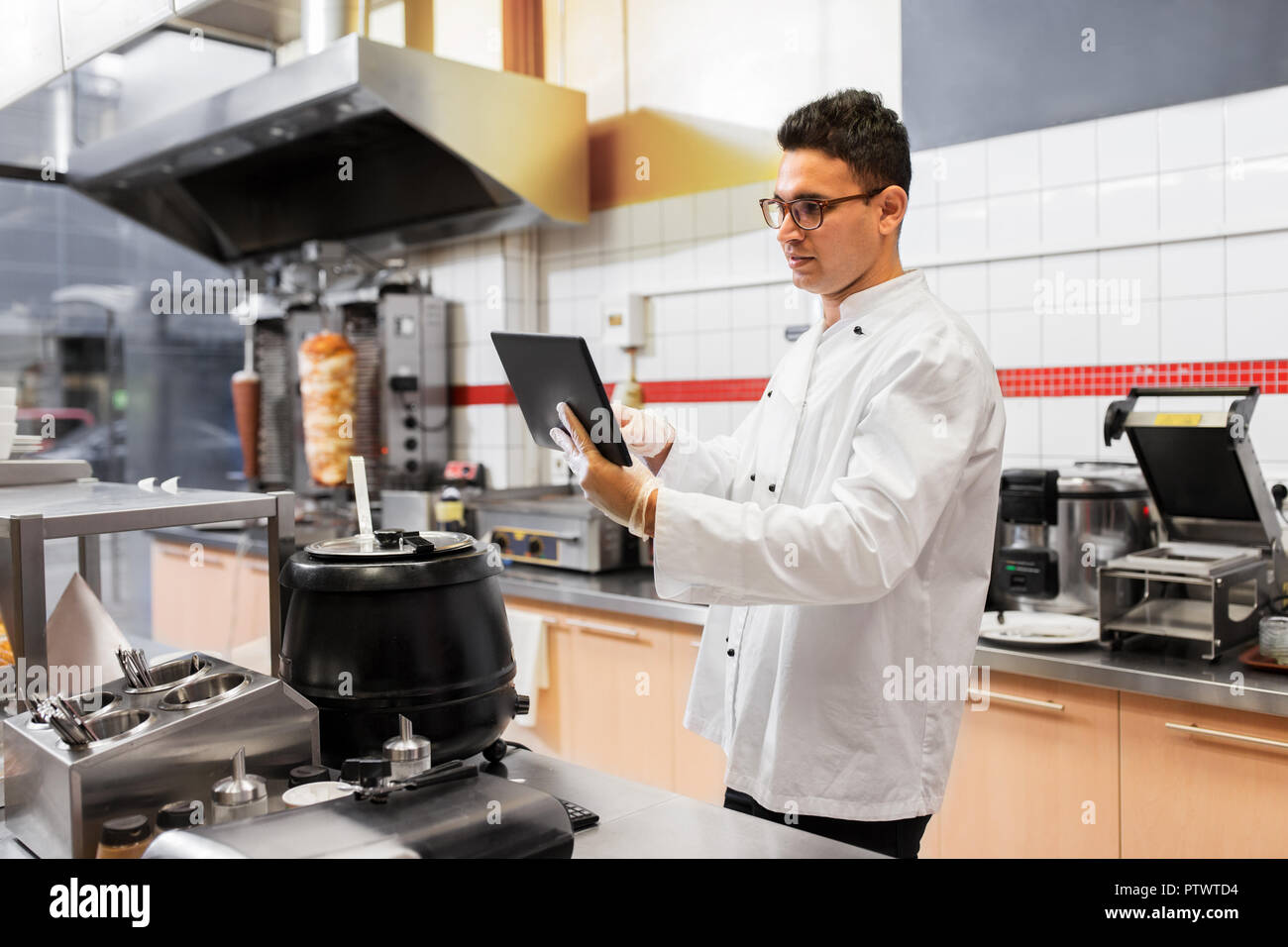 Koch Kochen mit Tablet-pc im Restaurantküche Stockbild