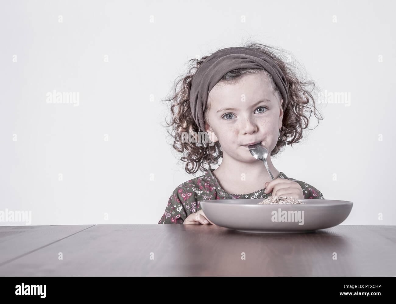 Näher Sitzt bin Tisch Mit Löffel Im Mund (Model-Release) Stockbild