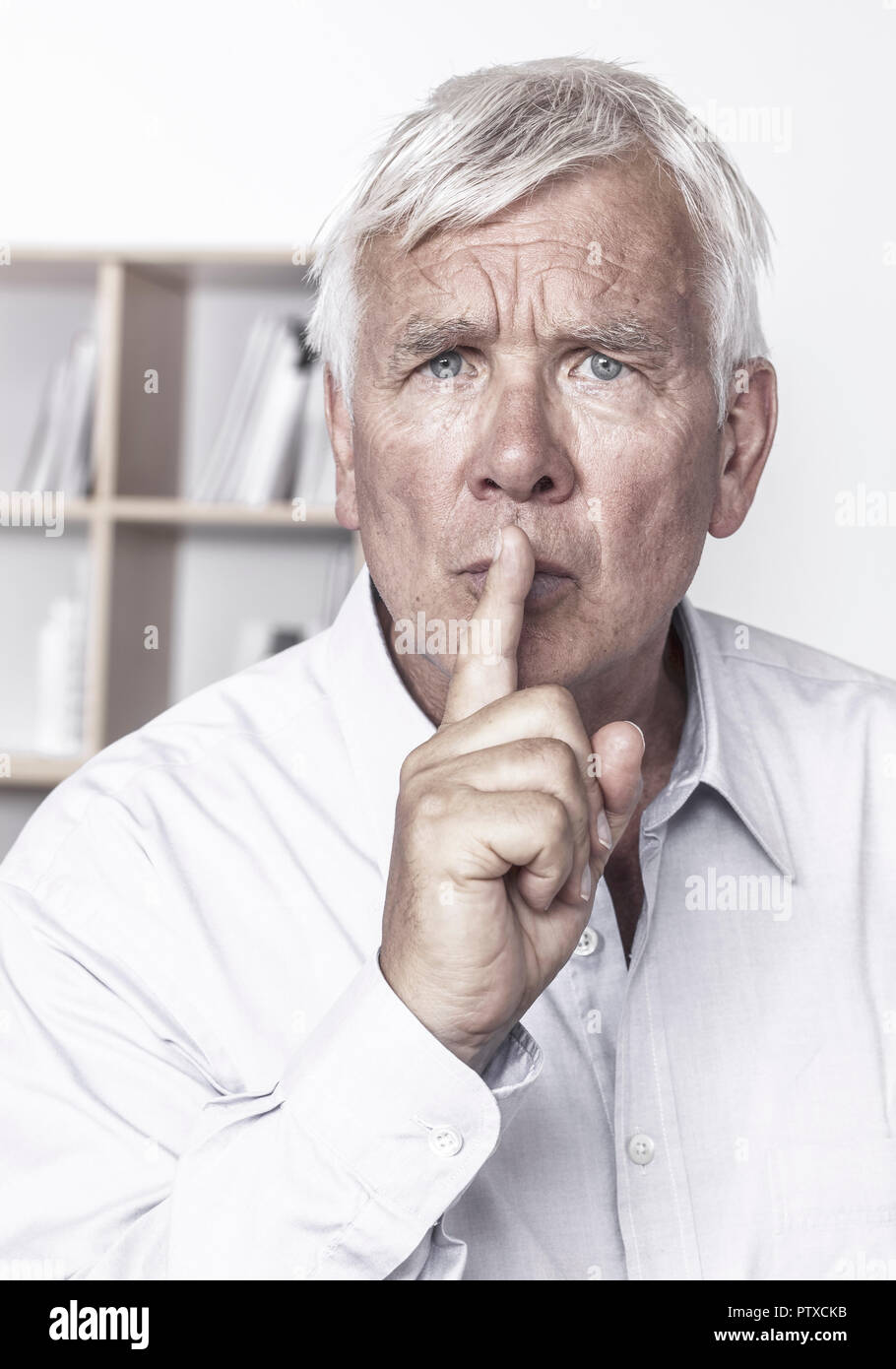 Senior Mit Gestik Finger Vor Dem Mund (Model-Release) Stockbild