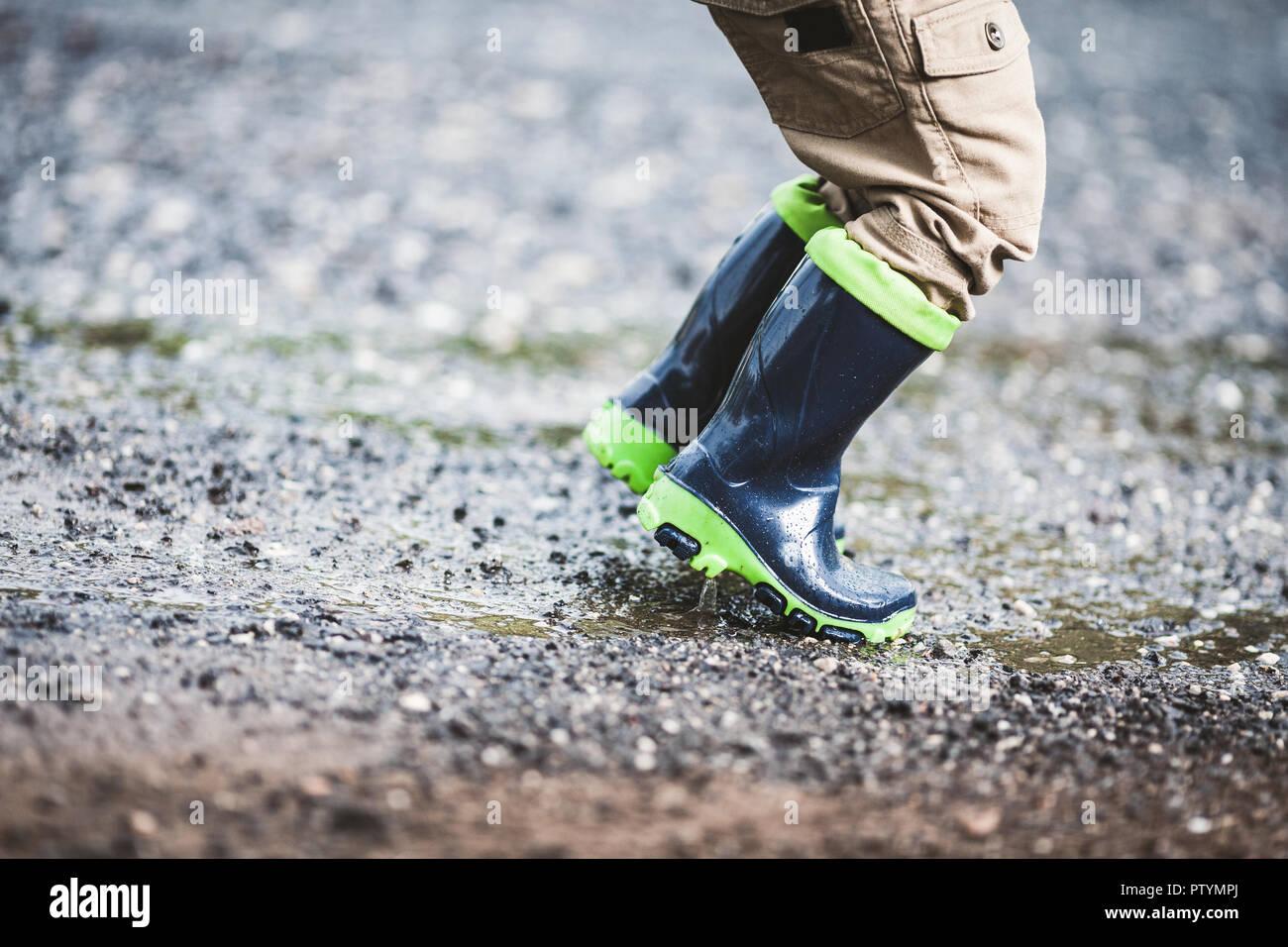 Nahaufnahme auf Kleinkind tragen Gummistiefel im regnerischen Wetter Stockfoto