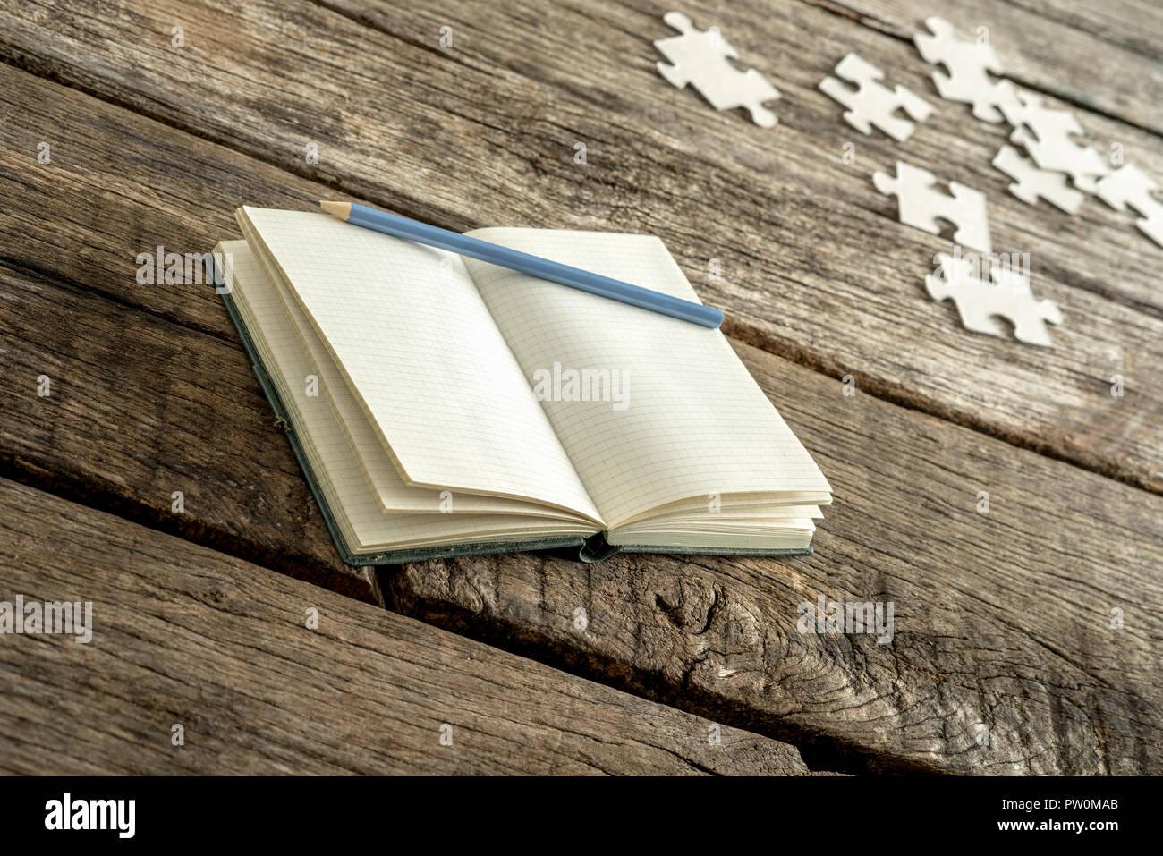 Leeres weißes Buch mit Bleistift und Puzzleteile über alten verwitterten Holztisch zum Thema über Erinnerungen und Selbstbeobachtung. Stockbild