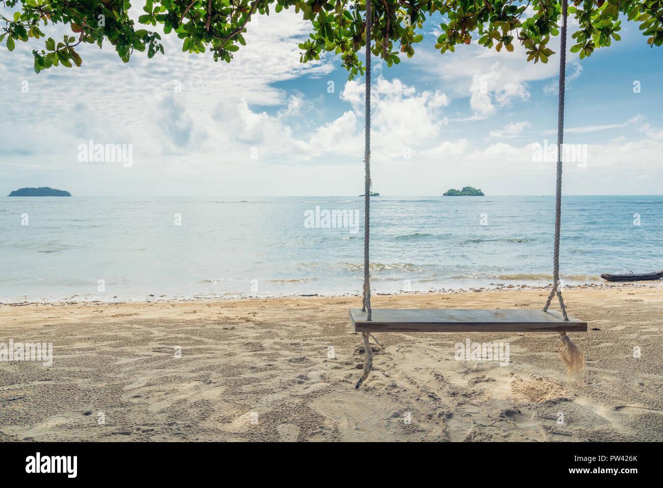 Holzschaukel Stuhl hängen am Baum in der Nähe von Strand von Island in Phuket, Thailand. Sommer Urlaubsreisen und Urlaub-Konzept. Stockbild