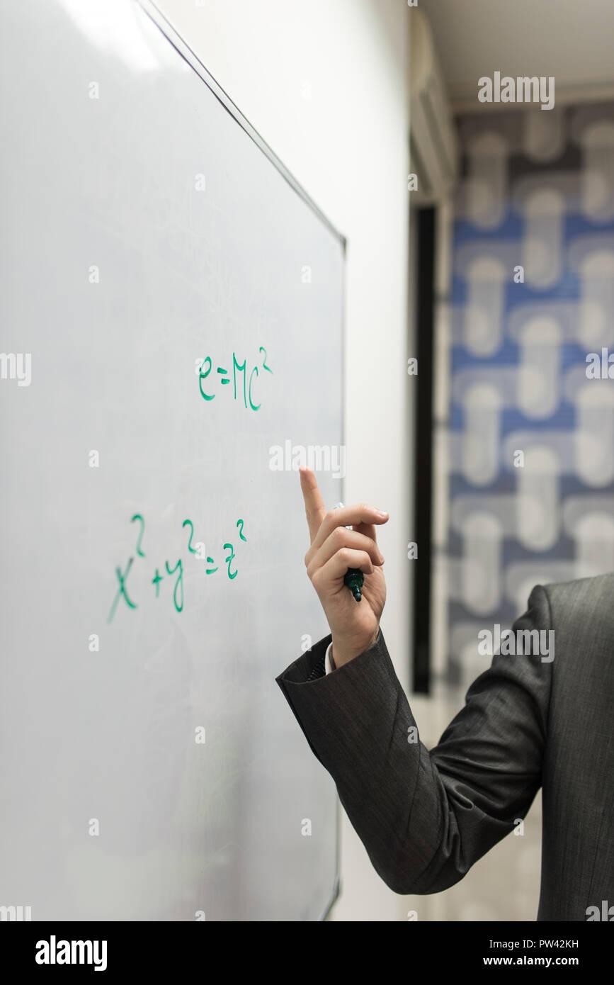 Nahaufnahme der Professor zeigt auf eine Masse Energie Gleichwertigkeit Formel auf eine Tafel geschrieben. Stockfoto