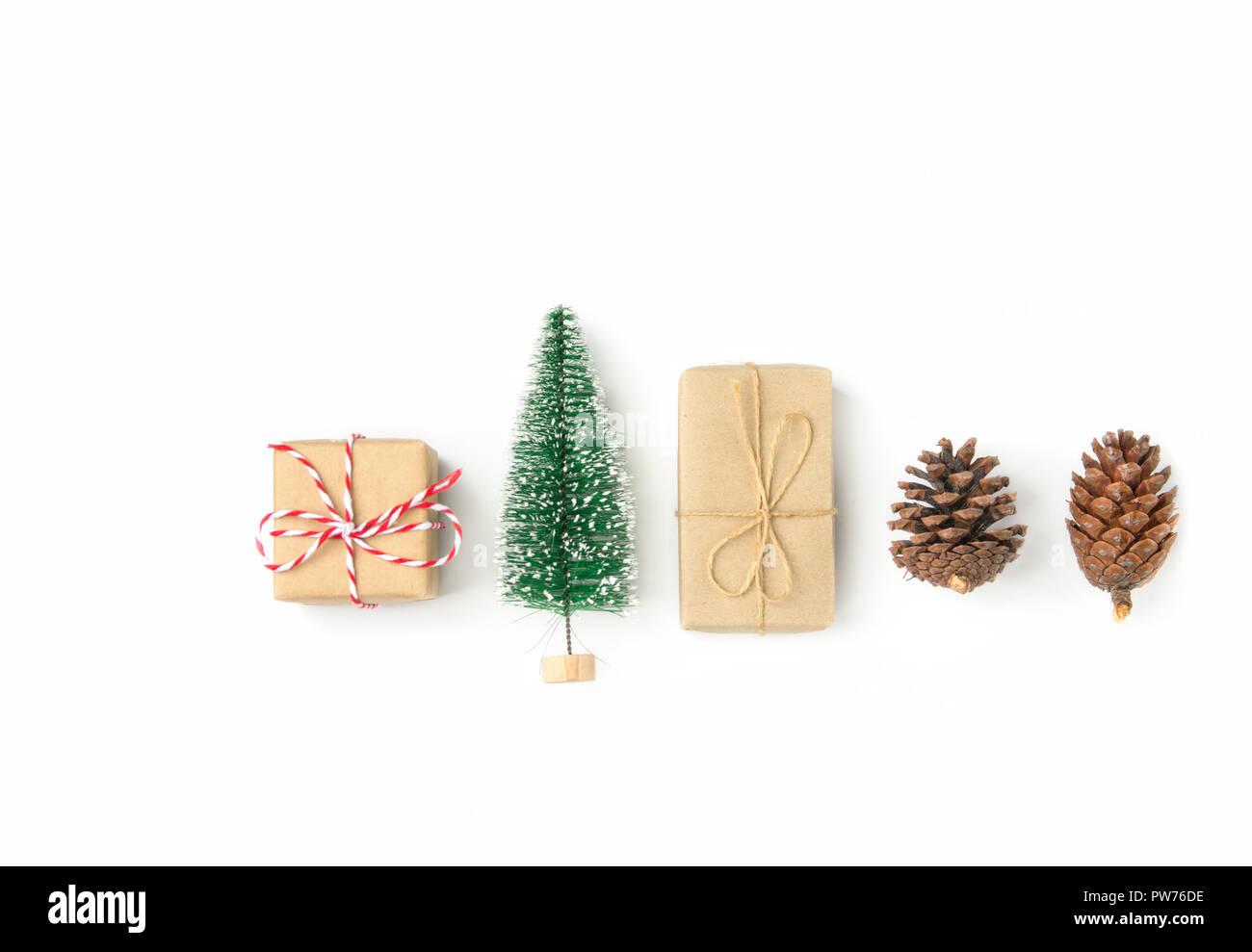 Geschenkboxen in Handwerk Papier Weihnachtsbaum gewickelt Tannenzapfen in Reihe auf festen, weißen Hintergrund angeordnet. Knolling flach. Neue Jahr präsentiert Urlaub pr Stockfoto