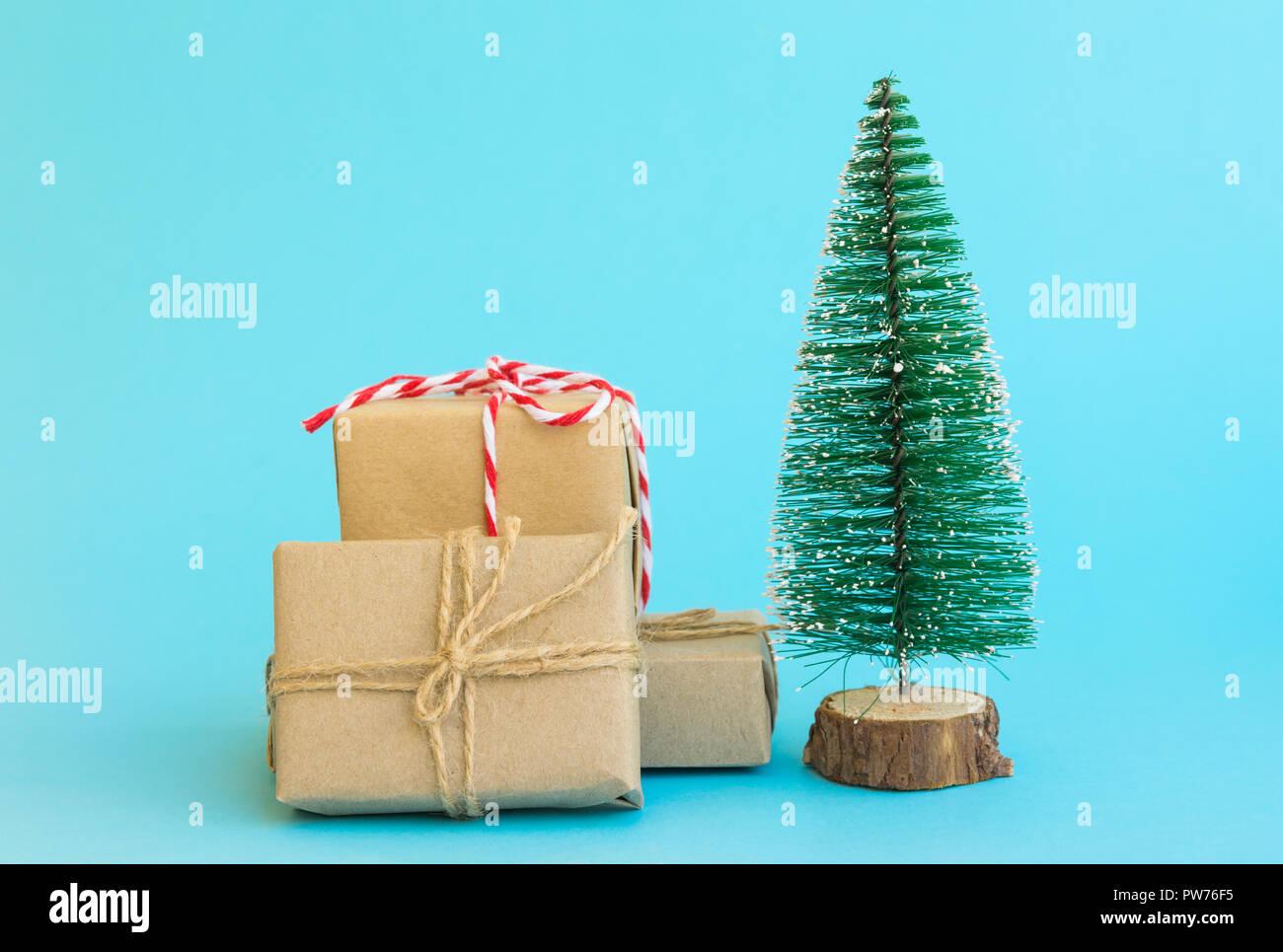 Stapel der Geschenkboxen in Handwerk Papier mit Garn rot weiße Band Weihnachtsbaum auf Mint blau hintergrund Band umwickelt. Neues Jahr corporate präsentiert shoppin Stockfoto