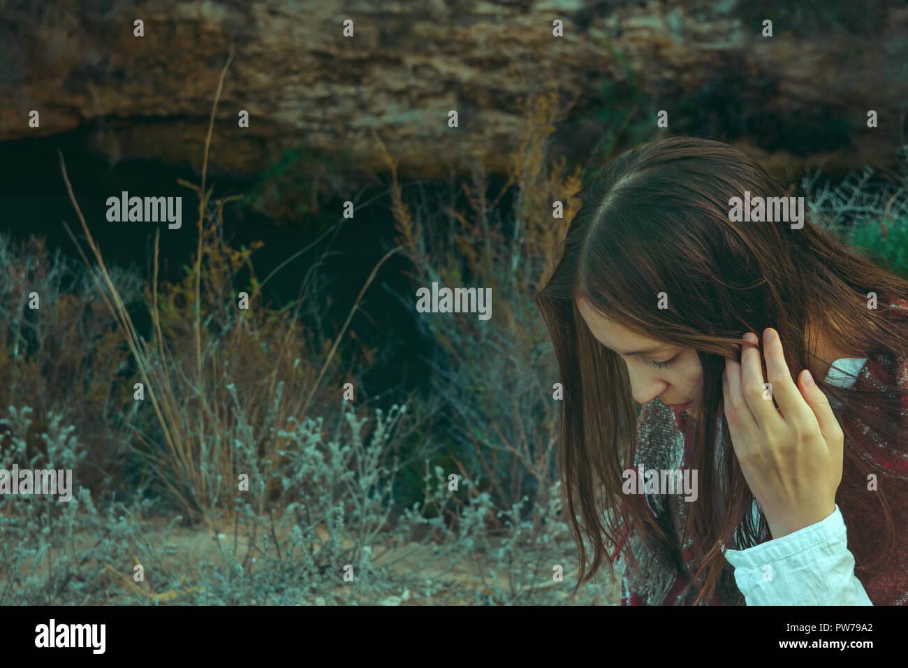 Junge kaukasier Frau mit langen kastanienbraunen Haare in karierten Wolle plaid Wandern in Feld Wiese. Gemütliche herbstliche Atmosphäre. Schöne Landschaft. Warme Erde Stockfoto