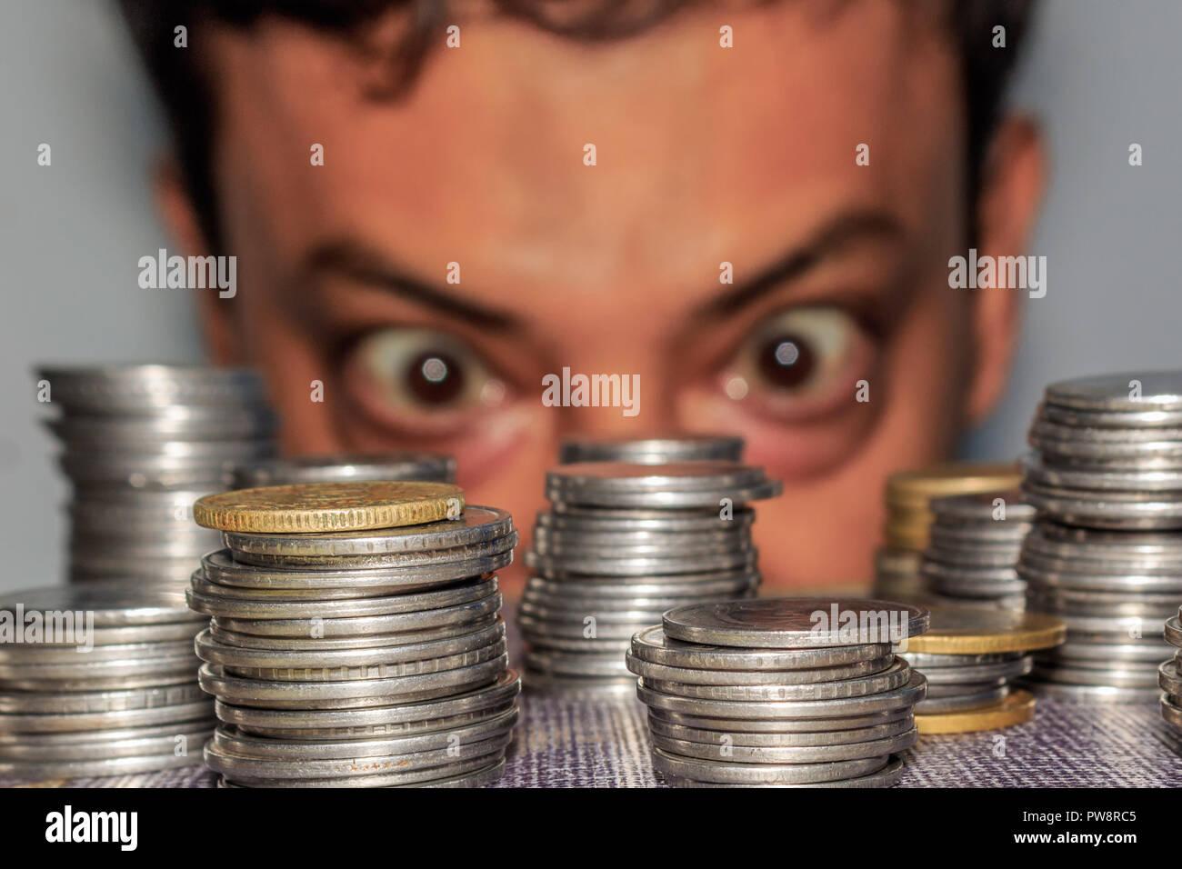 Fokus auf Münze. Ein reichhaltiges gierig älterer Mann schaut auf Münzen. Der Kollektor sieht seinen Reichtum. Ein älterer Mann in Metall Geld starrte auf den Boden. Stockbild
