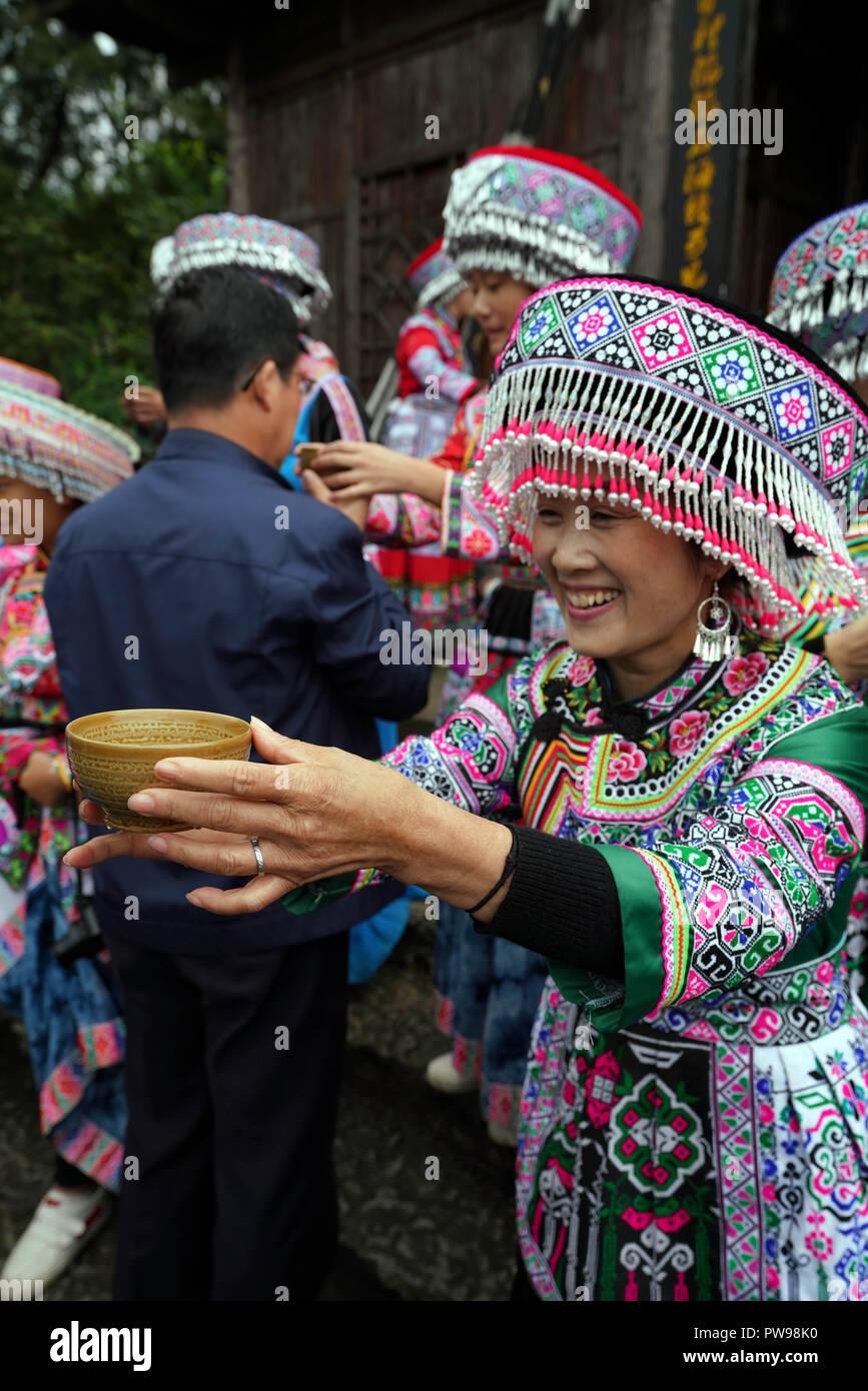 Die Provinz Sichuan, China. 14. Oktober 2018. Die Angestellten grüßen Touristen durch das Angebot von alkoholischen Getränken bei Xingwen UNESCO Global Geopark Xingwen Grafschaft von Yichang, Provinz Sichuan im Südwesten Chinas, Okt. 14, 2018. In den ersten drei Quartalen 2018 die Grafschaft hat einen Tourismus Einnahmen von 7,6 Mrd. Yuan (1,1 Quelle: Xinhua/Alamy Live Nachrichten hatten Stockbild