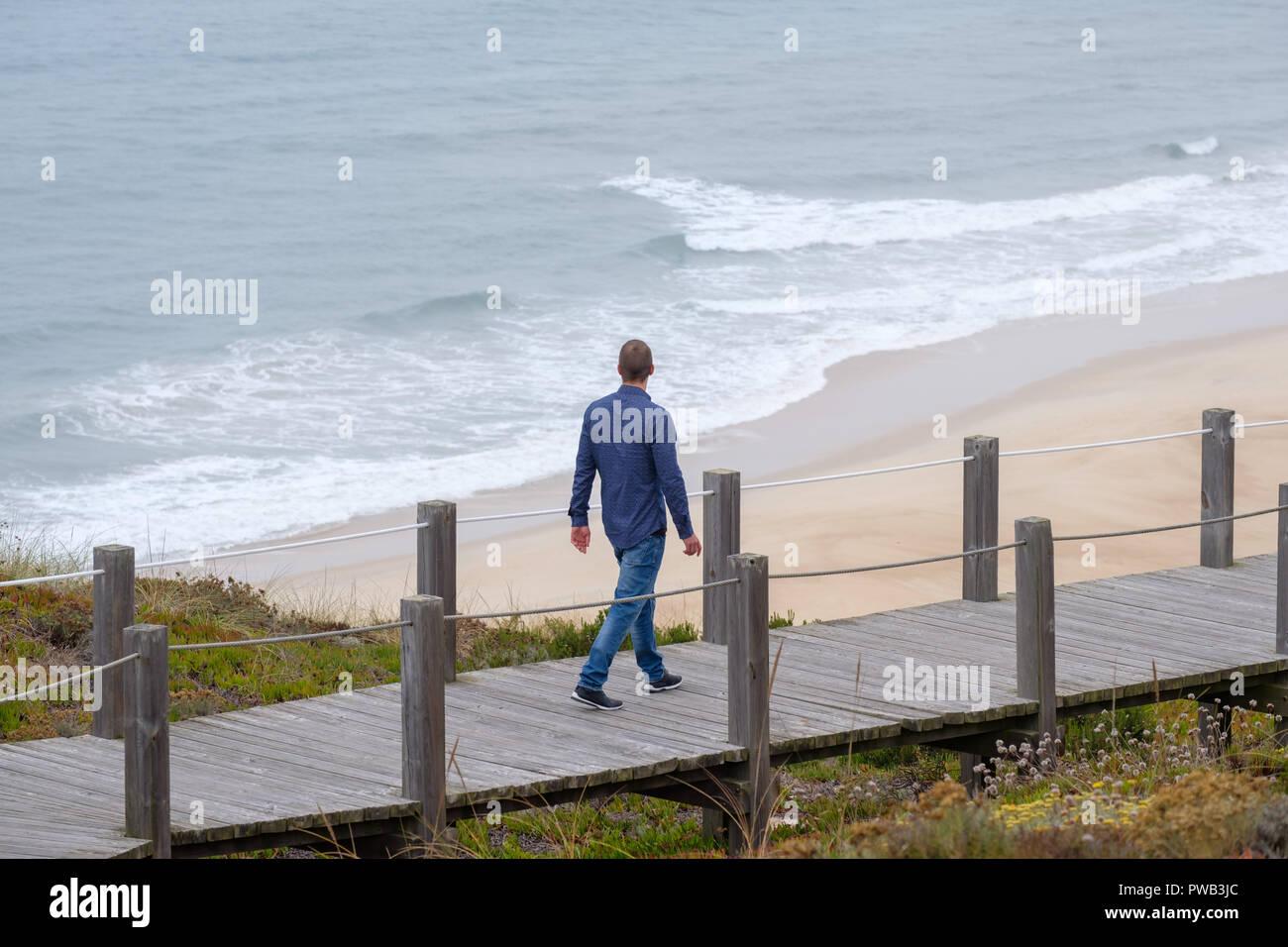 Mann zu Fuß auf eine Promenade am Strand bei kaltem Wetter Stockbild