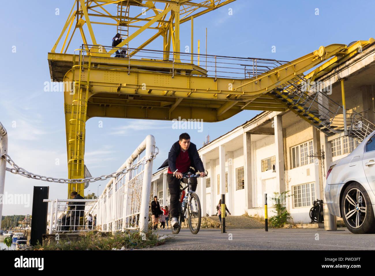 Man Radfahren entlang der Radweg auf dem Fluss Sava waterfront vorbei an dem gelben Kran der Belgrader Hafen. Stockbild