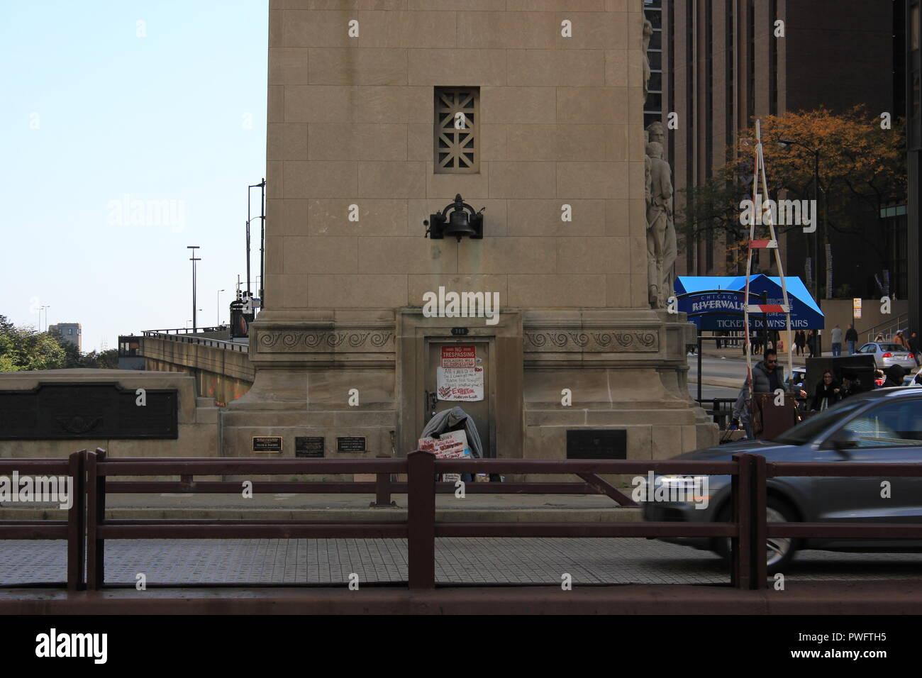 Obdachlosen sitzen auf der Michigan Avenue Bridge auf einem kalten Herbst Tag warten auf ein Arbeitsblatt. Stockbild