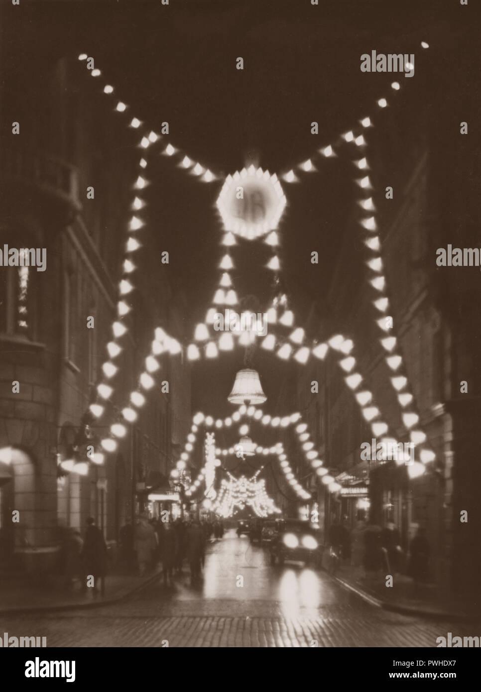 Weihnachten in den 1930er Jahren. Die belebte Straße Biblioteksgatan mit Weihnachtsbeleuchtung dekoriert ist. Das elektrische Licht und die Weihnachtsdekorationen schafft eine schöne Weihnachten. Schweden 1930 Stockbild