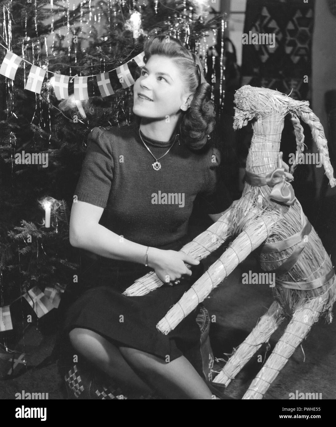 Weihnachten in den 1940er Jahren. Die jungen Eiskunstlauf Britta Råhlen feiert Weihnachten zu Hause in den 1940er Jahren. Sie hält eine traditionelle Stroh Ziege, als sie durch den Weihnachtsbaum sitzt. Schweden 1940. Stockbild