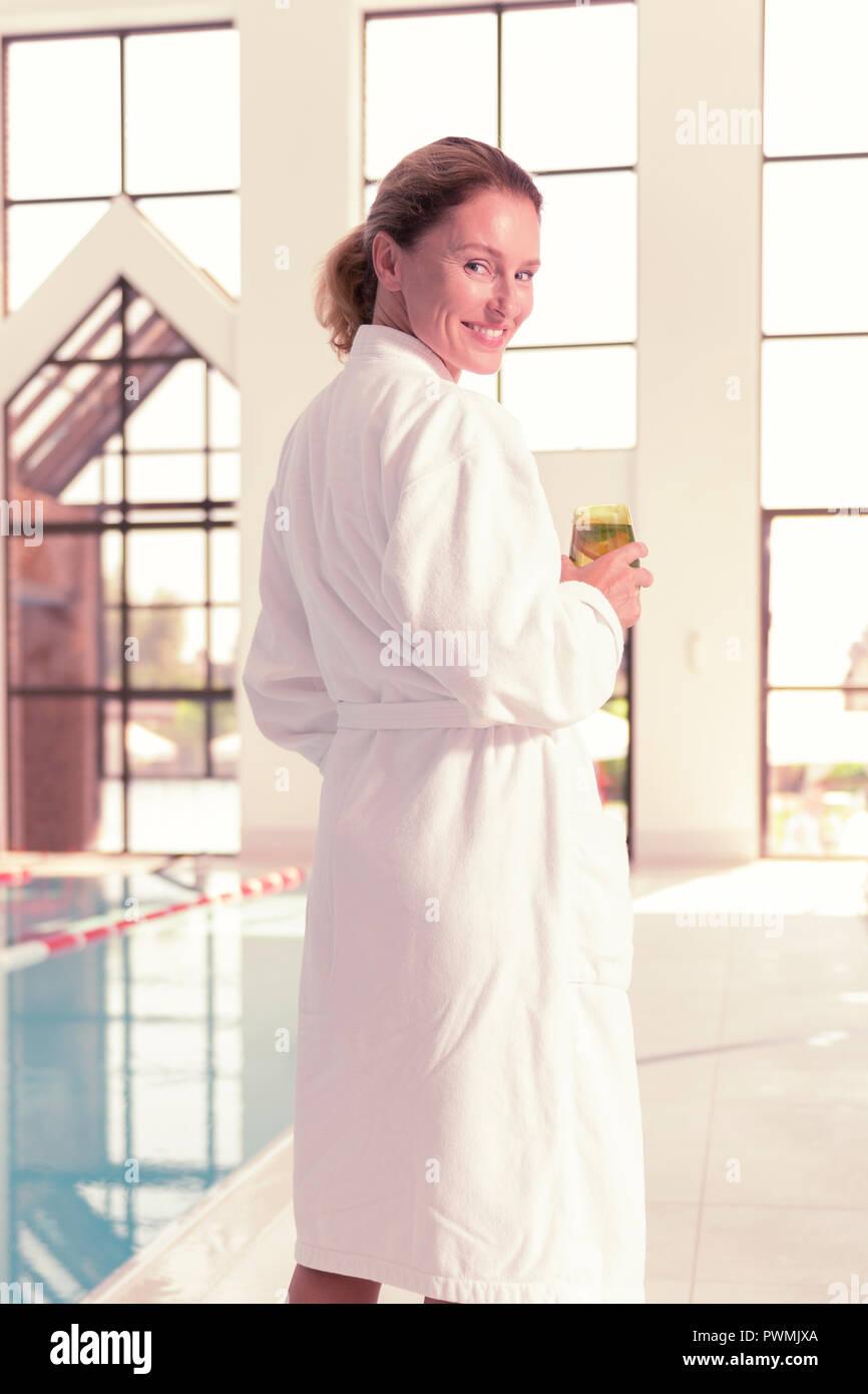 Freundliche nette Frau trägt ein weißes Gewand Stockbild