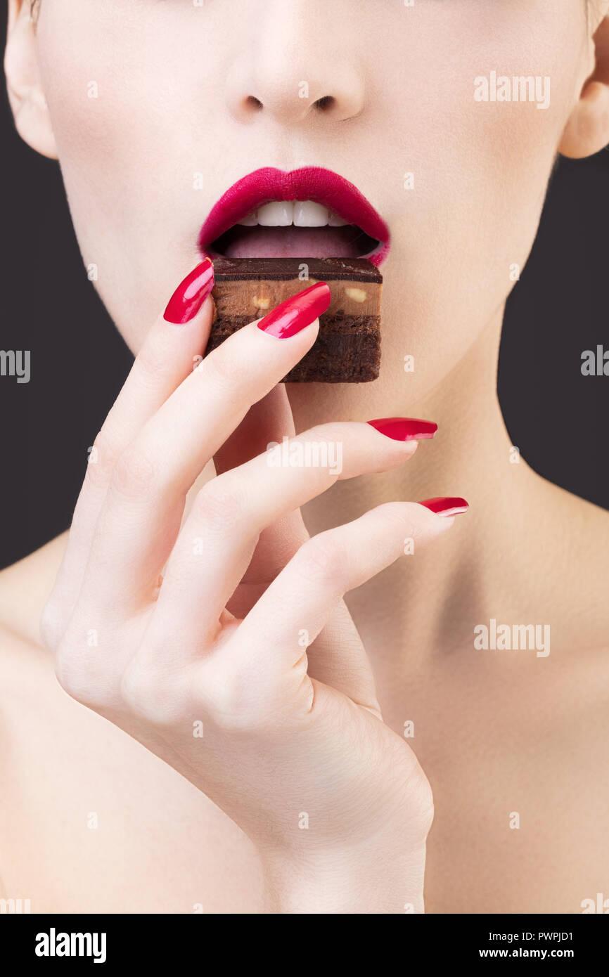 Enge Schoß des Mädchens schmeckende Schokolade Kuchen Stockbild