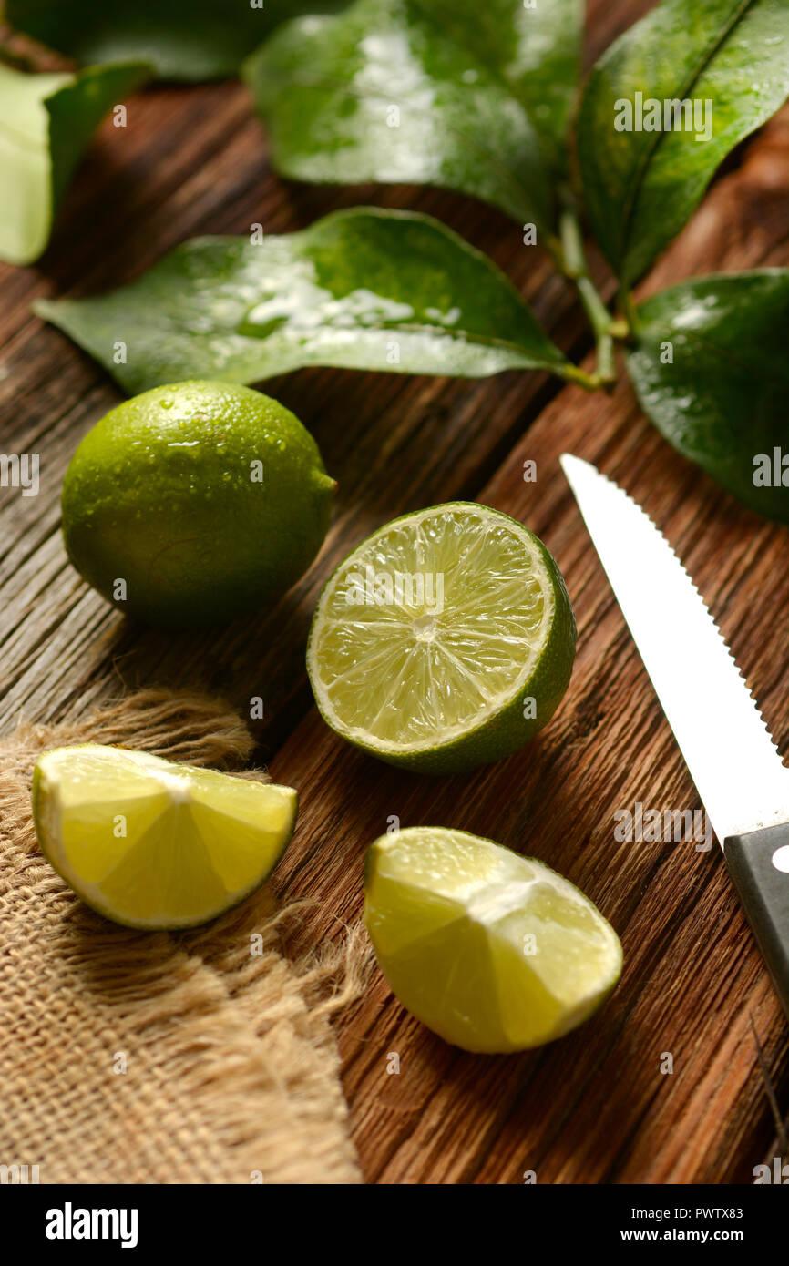 Kalk Früchte und Blätter auf Holztisch - tropische Früchte mit antioxidativen Eigenschaften: Detailansicht Stockfoto