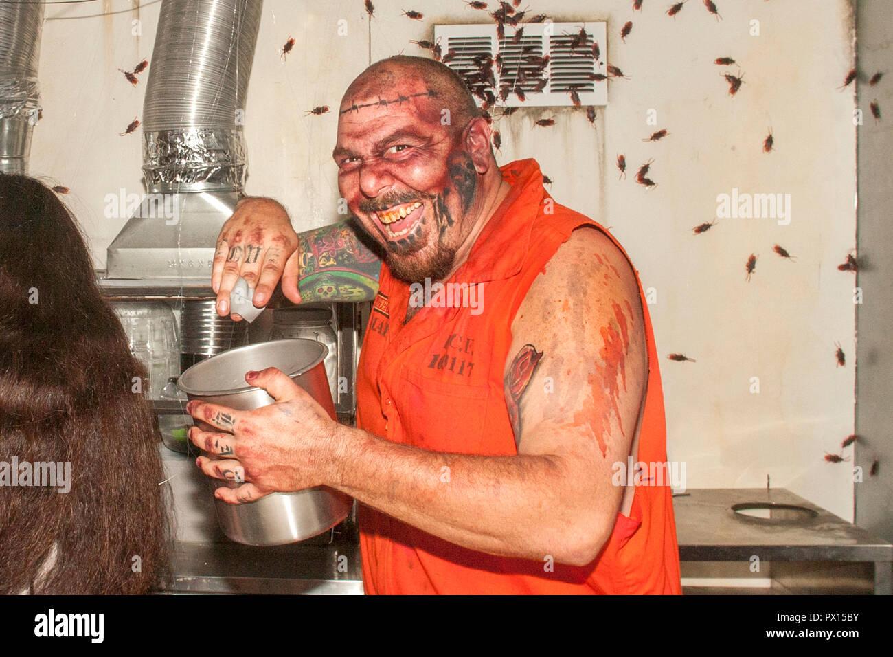 """Mit einem bösen Lachen, """"der Gefangene"""" auf der 17. Tür Halloween haunted House in Fullerton, CA, bereitet die Bugs auf Besucher zu zufügen. Stockbild"""