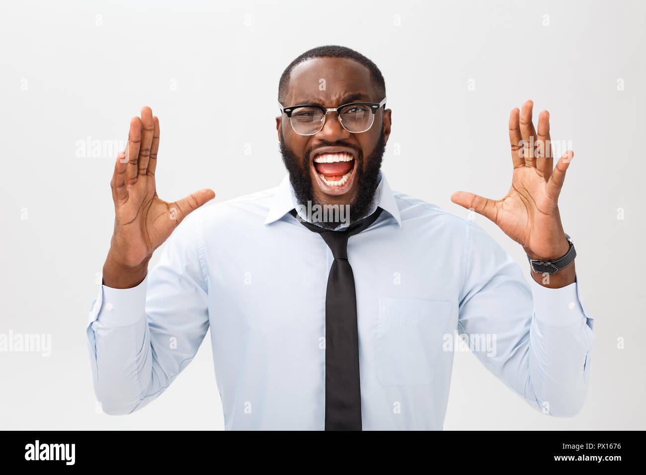 Portrait von verzweifelten genervt männlichen Schwarzen schreiend in Wut und Zorn seine Haare reißen aus, während das Gefühl wütend und Mad mit etwas. Negative menschliche Gesicht Ausdruck, Emotionen und Gefühle. Stockfoto
