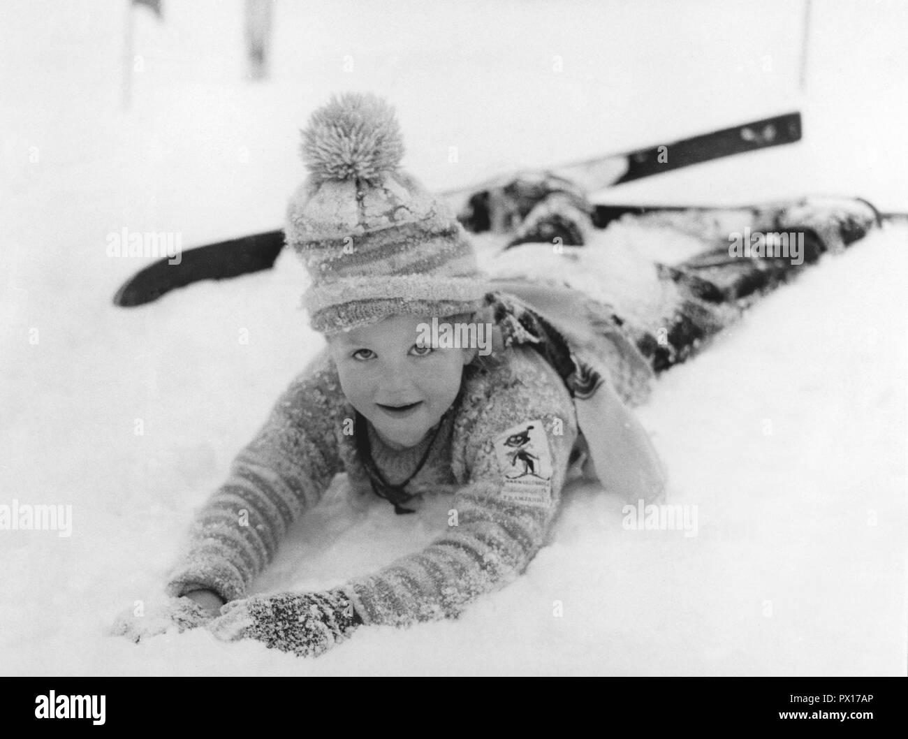 Winter in den 50er Jahren. Ein Mädchen in der Skischule liegt im Schnee. Schweden 1950 Stockbild
