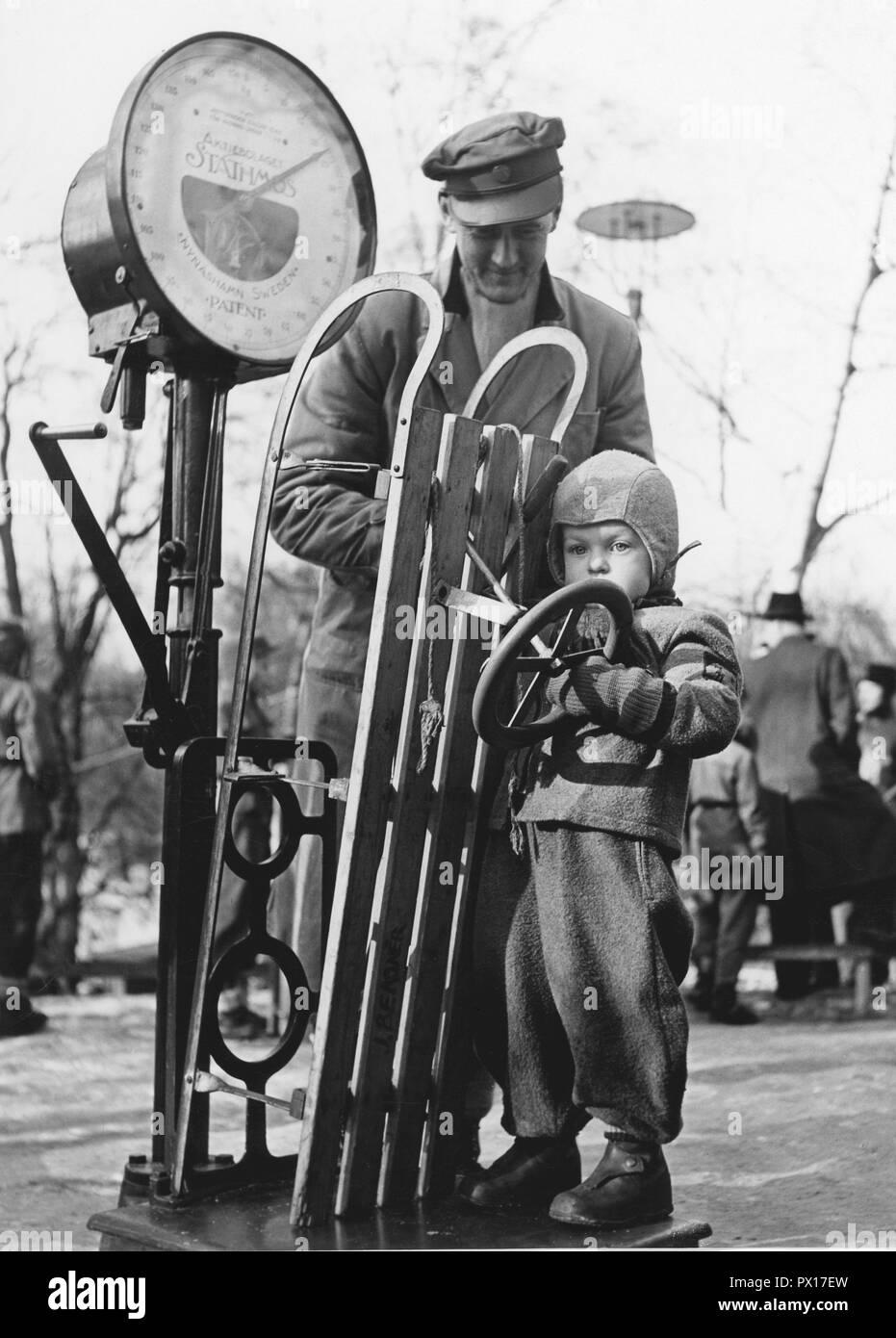 Schlitten in den 1950er Jahren. Ein kleines Kind steht auf einer Skala zusammen mit dem Schlitten. Schweden 1950. Stockbild