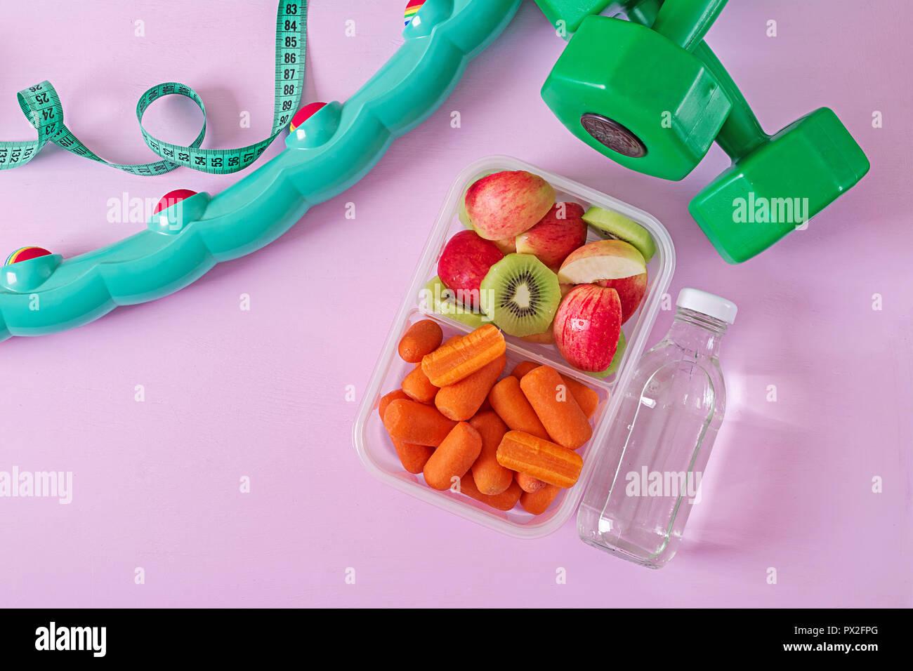 Fitnessgeräte. Gesundes Essen. Konzept gesunde Ernährung und Sport Lifestyle. Vegetarisches Mittagessen. Hantel, Wasser, Früchte auf rosa Hintergrund. Ansicht von oben. Fl Stockbild