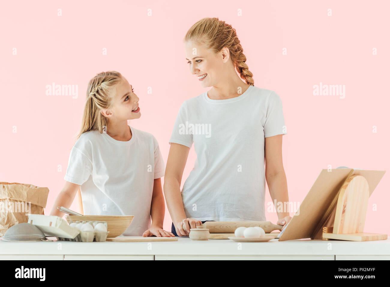 Lächelnde Mutter und Tochter in den weißen T-Shirts sich einander beim Kochen gemeinsam auf rosa isoliert Stockbild