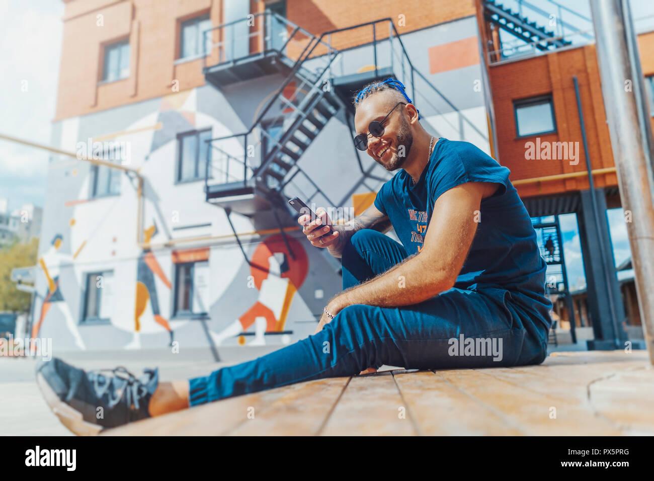 Jungen attraktiven Mann mit blauen Dreadlocks auf Handy Bildschirm schaut. Stockbild
