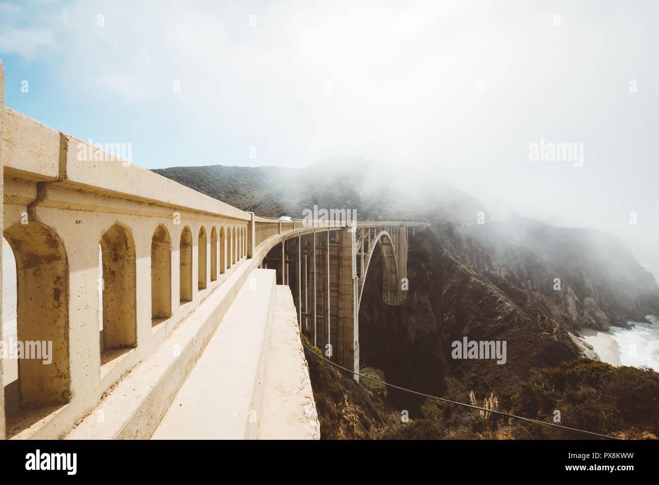 Panoramablick auf das historische Bixby Creek Bridge entlang der berühmten Highway 1 an einem sonnigen Tag mit Nebel im Sommer, Monterey County, Kalifornien, USA Stockbild