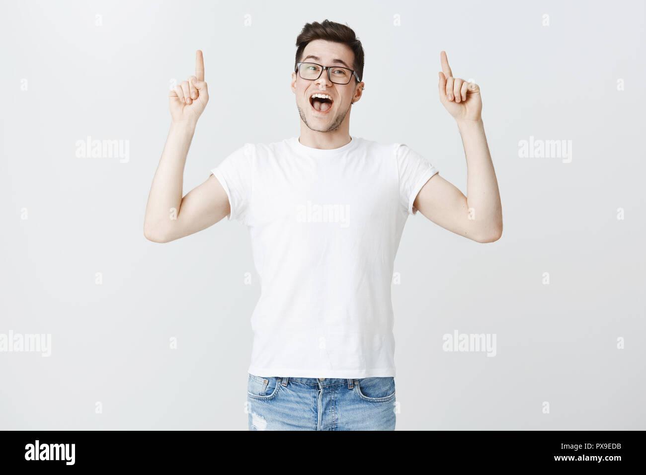Kiefer fällt als Hebeln fällt. Portrait von beeindruckt aufgeregt und freudig attraktiven jungen männlichen Freund heben die Hände oben mit überschnittenen Kiefer und überrascht positiv Lächeln gegen grauen Hintergrund posiert Stockfoto