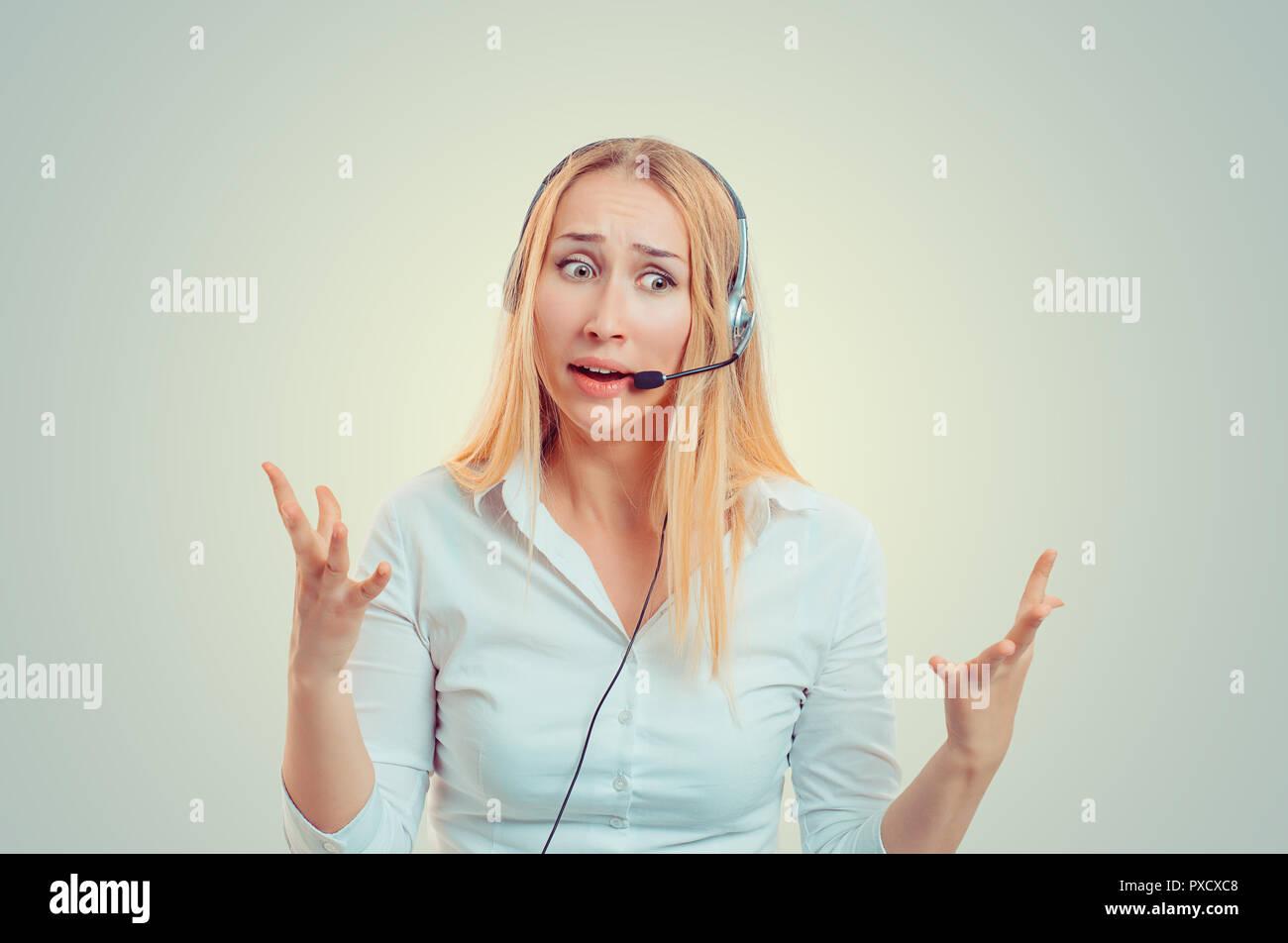 Junge blonde Frau in weißem Hemd Tragen des Headsets in Verwirrung und gestikulierend in Hilflosigkeit Stockbild