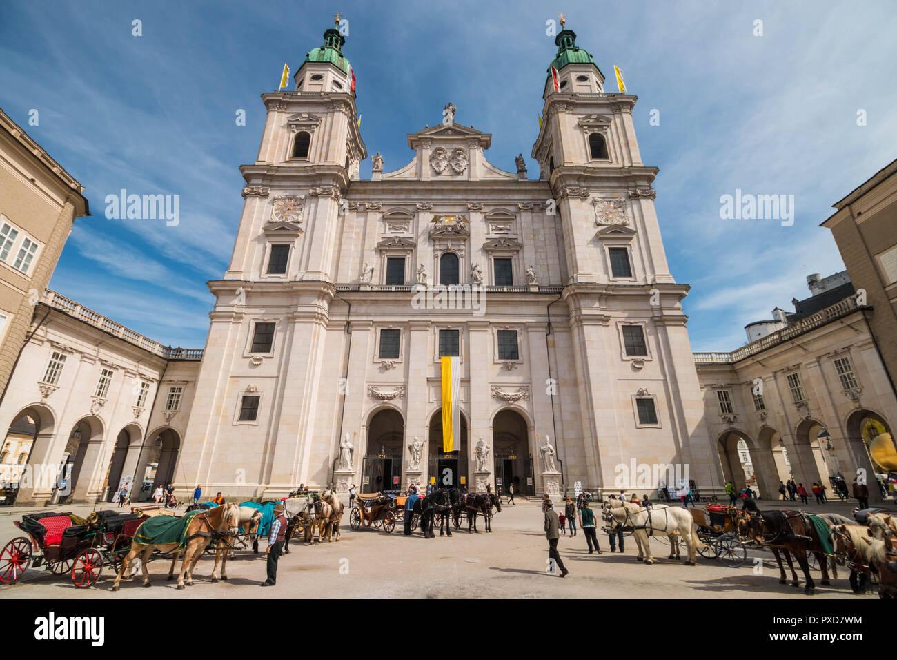Salzburg, Österreich - April 6, 2018: Viele Pferdekutschen mit schönen Pferde vor dem Salzburger Dom mit Domplatz geparkt warten zu geben Stockbild