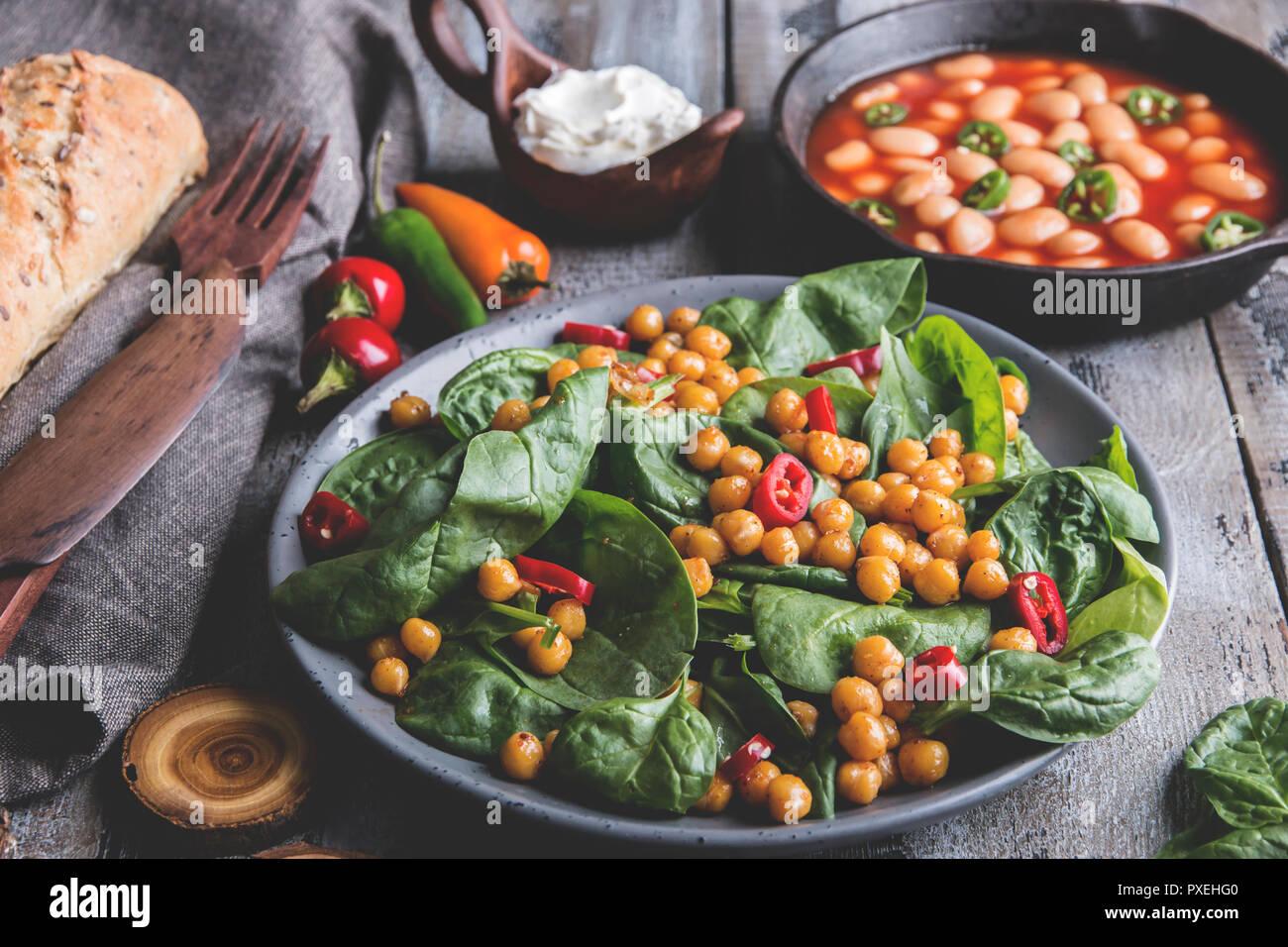 Kichererbsen und Gemüse Salat mit Spinat Blätter, gesund Hausgemachte veganes Essen, Diät. weiße Bohnen in Tomatensoße Stockbild