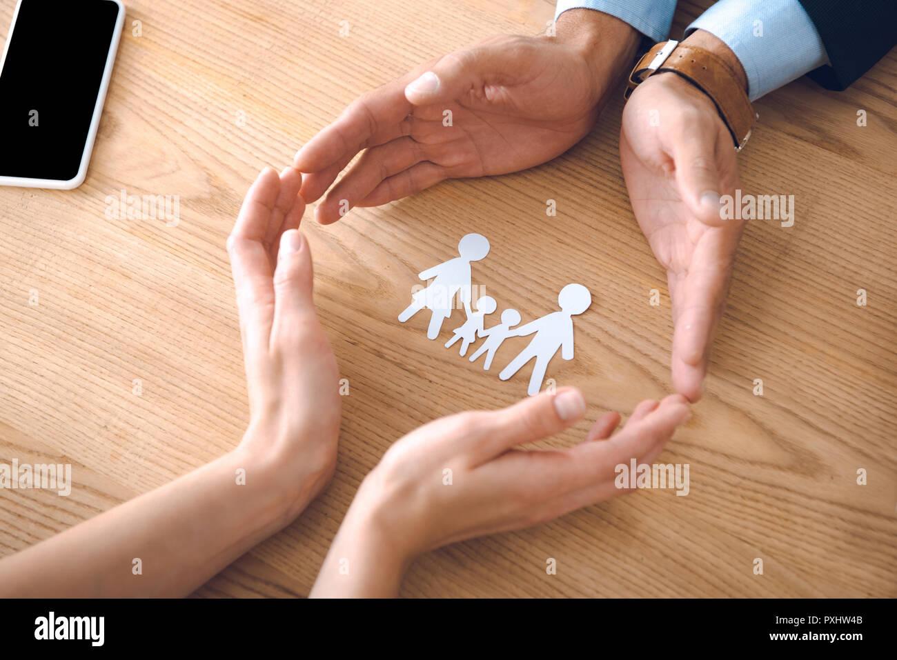 Teilansicht des Versicherungsagenten und weibliche Hände mit Familie Papier Modell auf hölzernen Tischplatte, Familie Versicherung Konzept Stockbild
